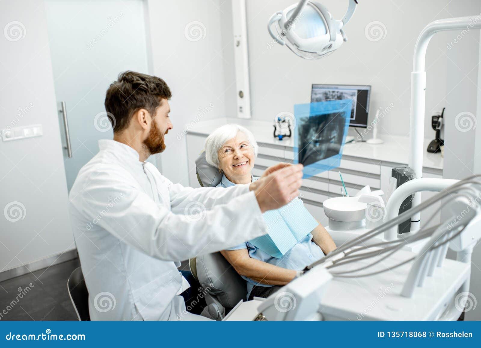 Dentysta pokazuje promieniowanie rentgenowskie stara kobieta w dentall biurze
