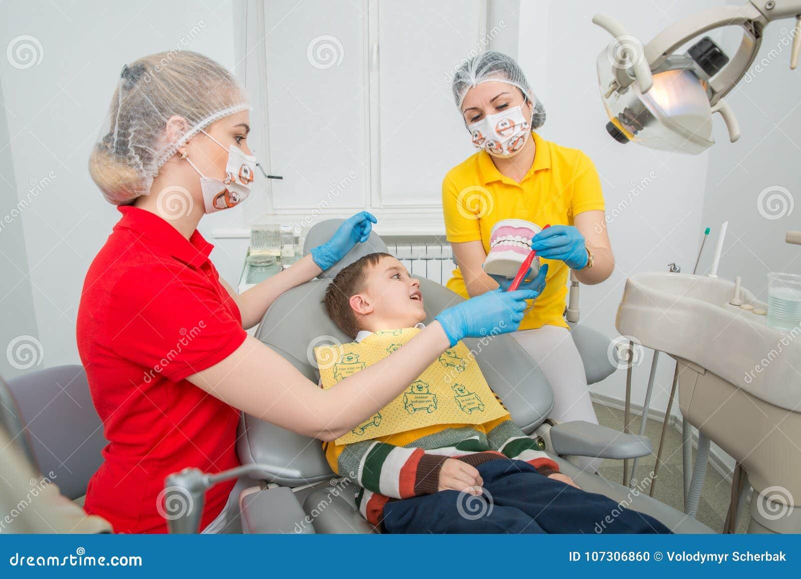 Dentysta z asystentem pokazuje chłopiec dlaczego czyścić zęby z toothbrush na sztucznej szczęki atrapie