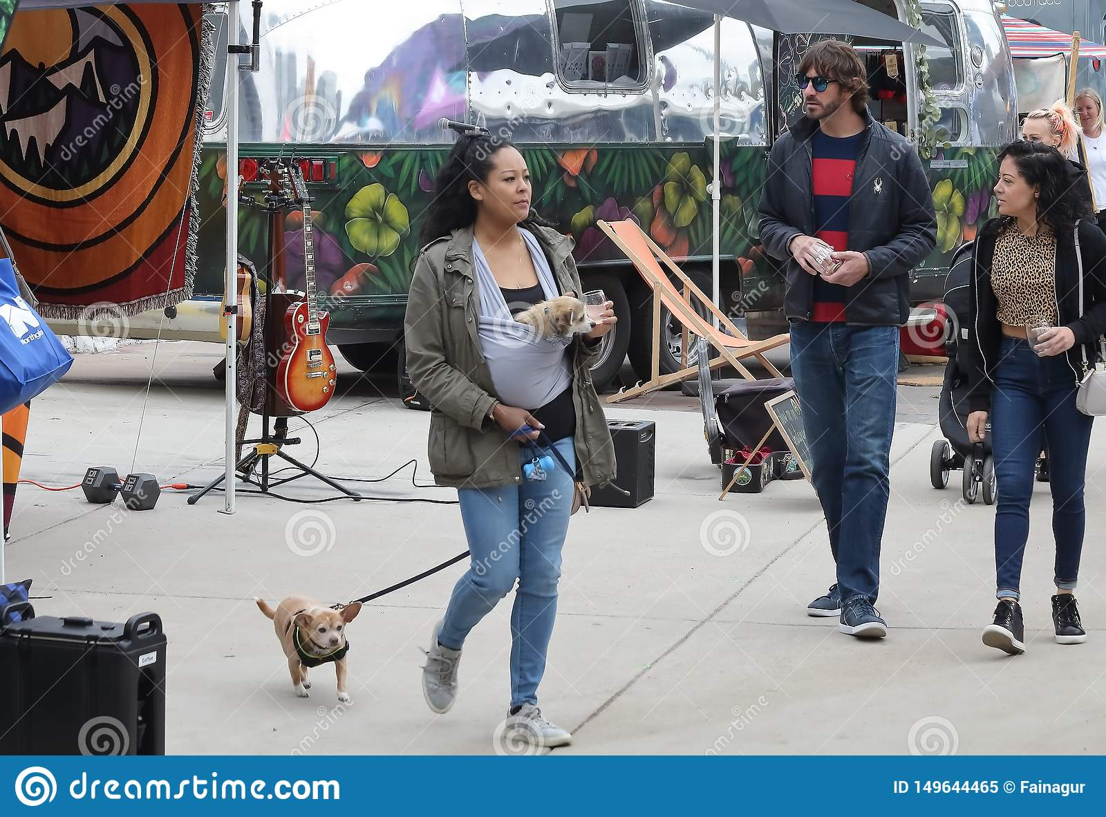 A woman with two dogs, one in a chest carrier and another on a leash walks at the Spring Bazaar in RINO Art District