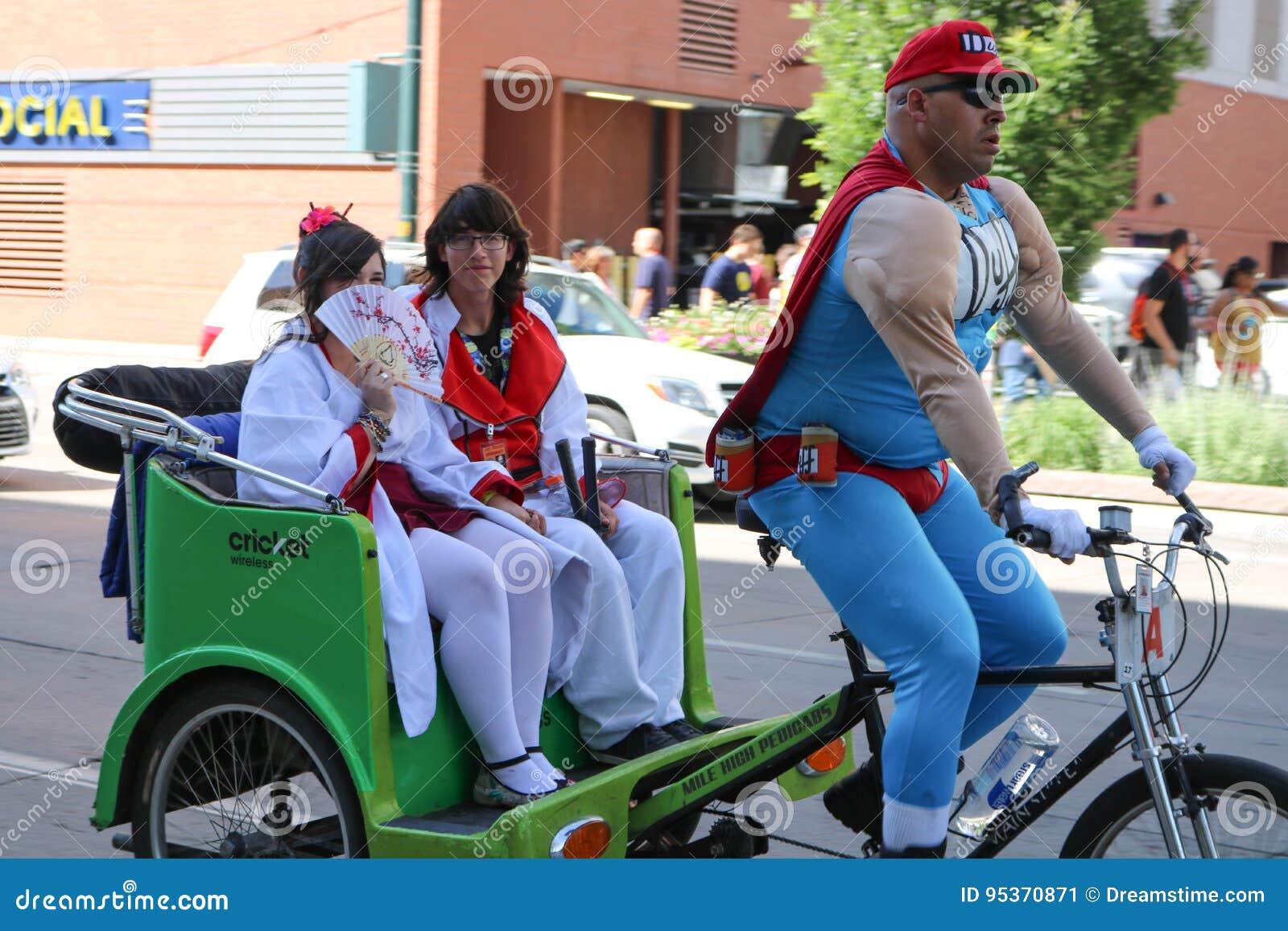 Denver, Colorado, USA - July 1, 2017: Duffman driving two geishas in a pedicab at Denver Comic Con