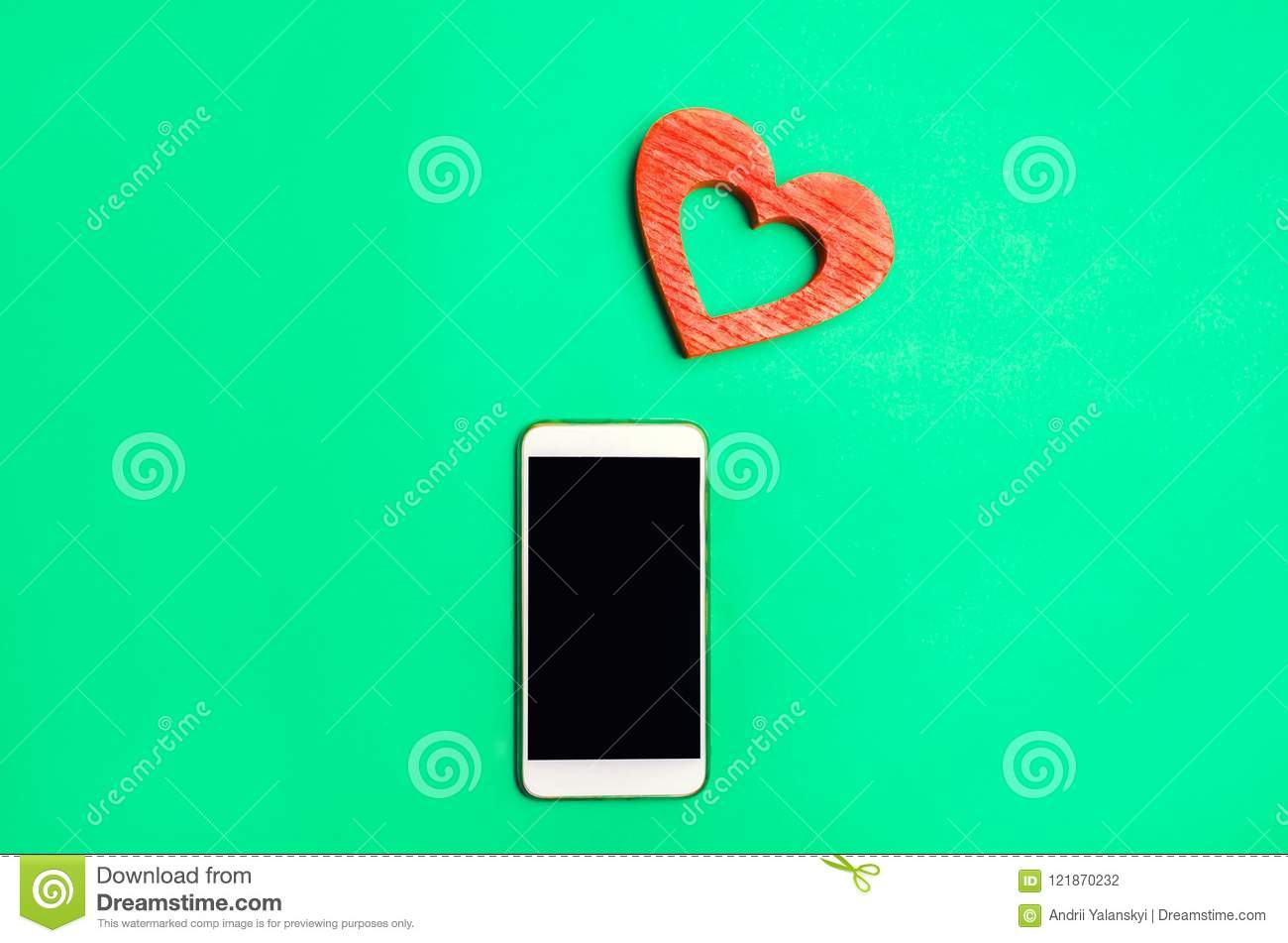 Dependence on social networks. phone smartphone and heart on a green background. online dating, flirting, message and calling your