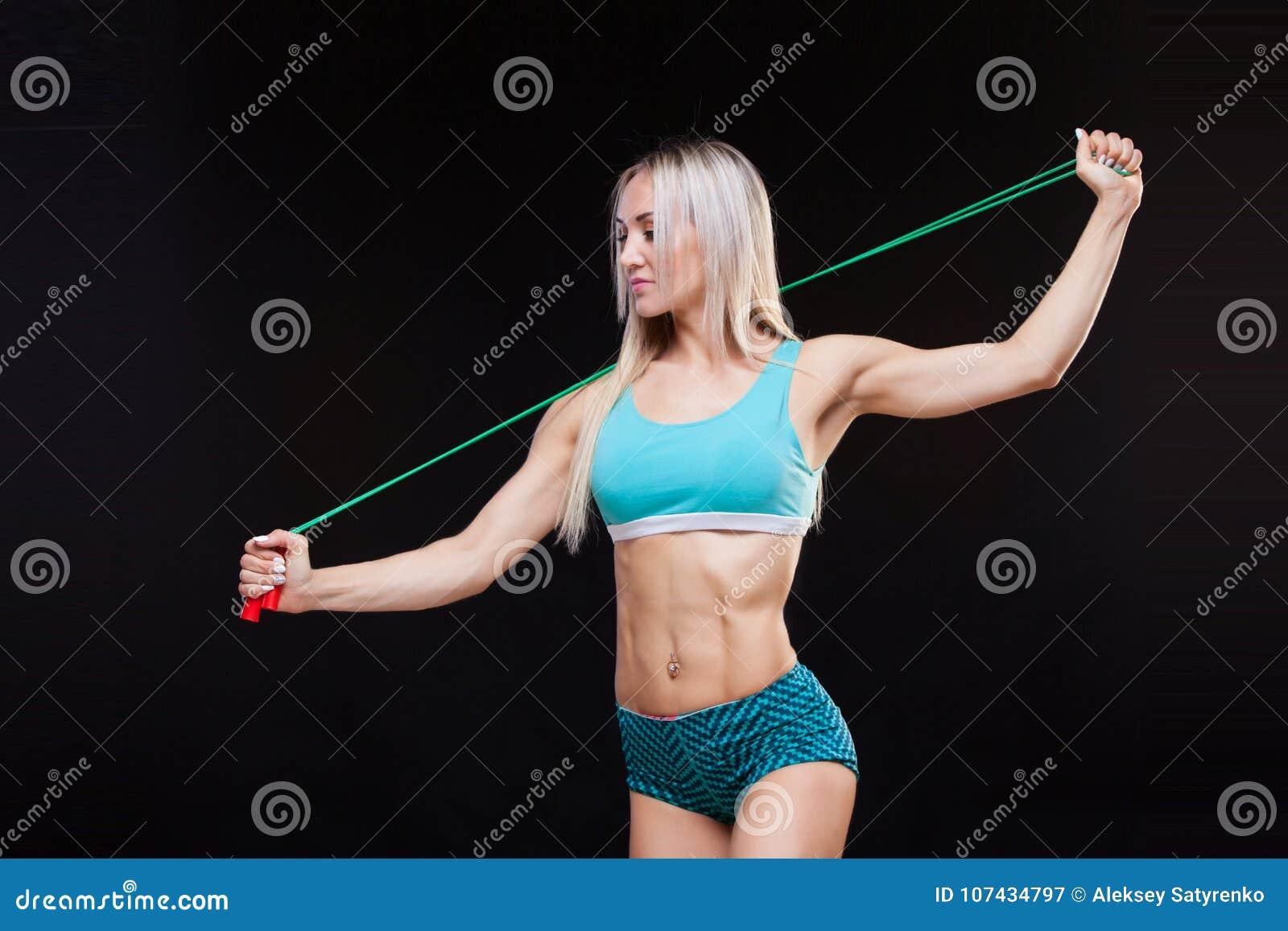 Deporte, actividad Mujer linda con la cuerda que salta Fondo muscular del negro de la mujer