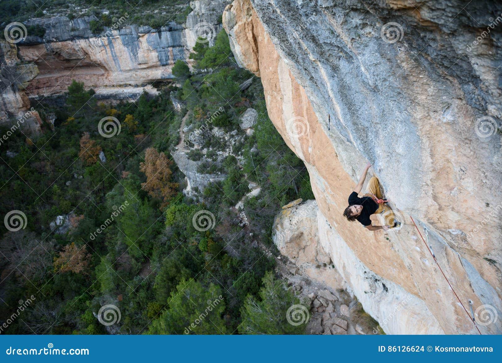 Deporte al aire libre Escalador de roca que tiene un resto en un acantilado El subir extremo del deporte