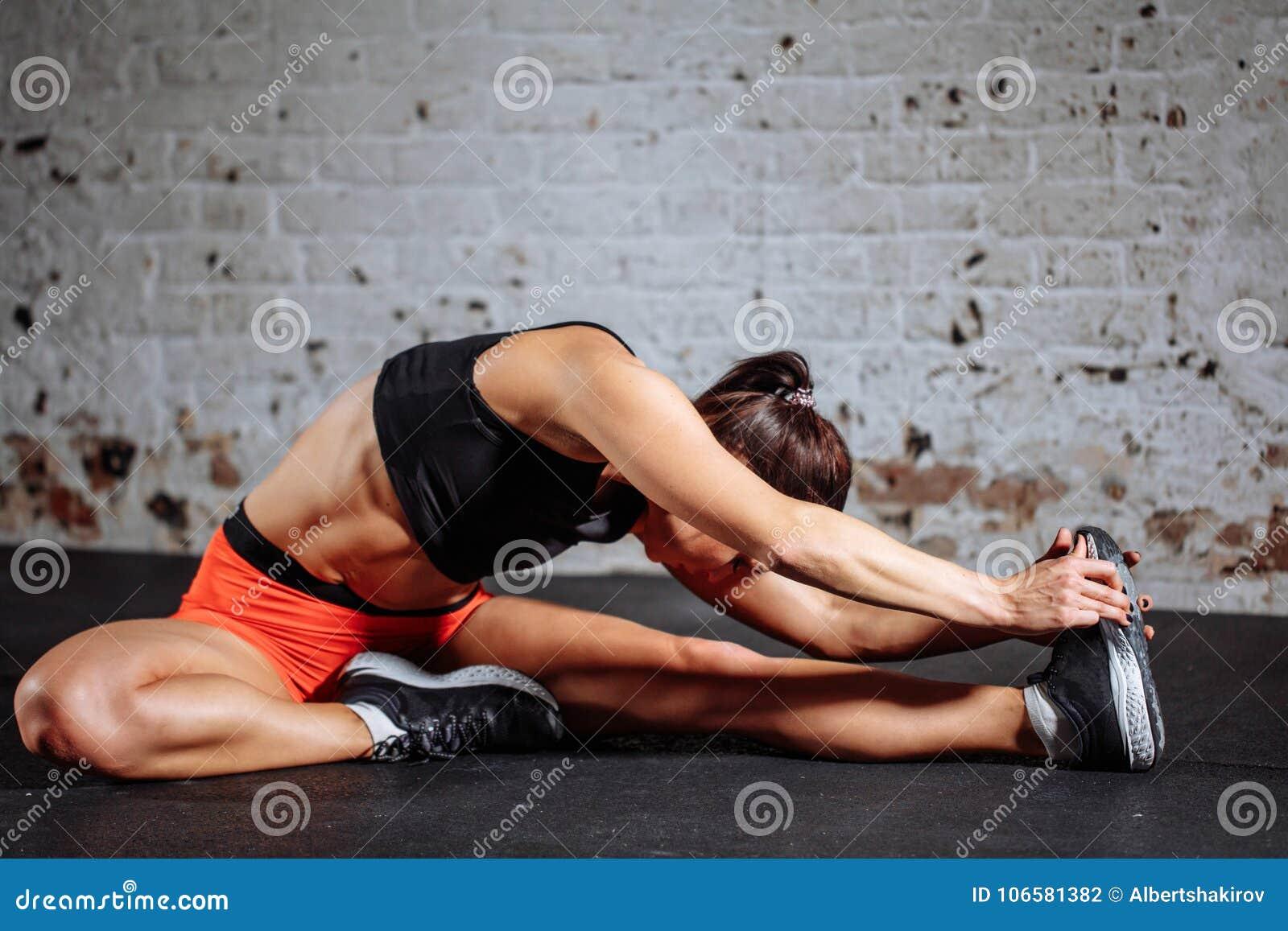 Deporte de la mujer que estira en gimnasio con la pared de ladrillo y las esteras negras