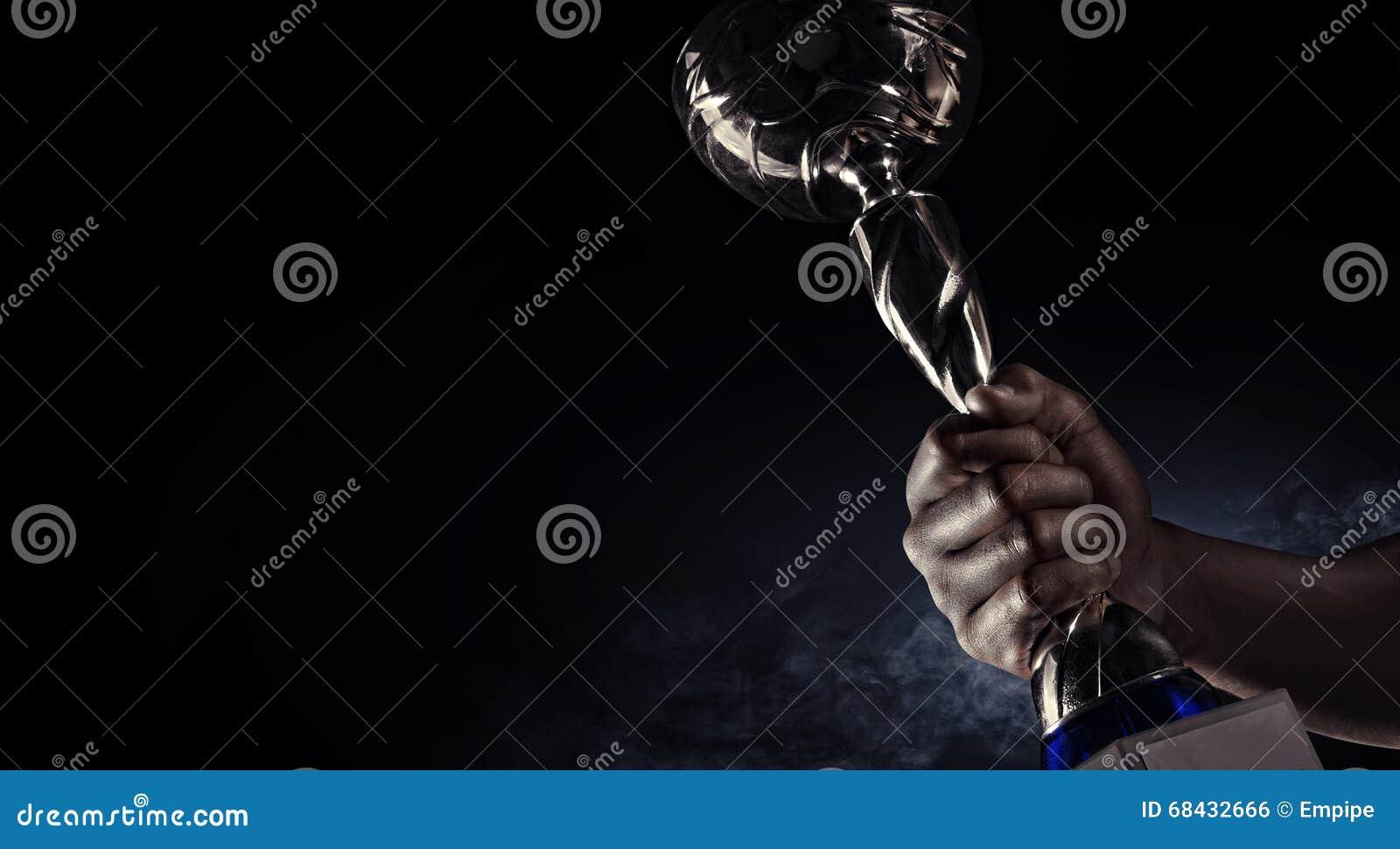 Deporte Man& x27; mano de s que soporta una taza del trofeo del oro