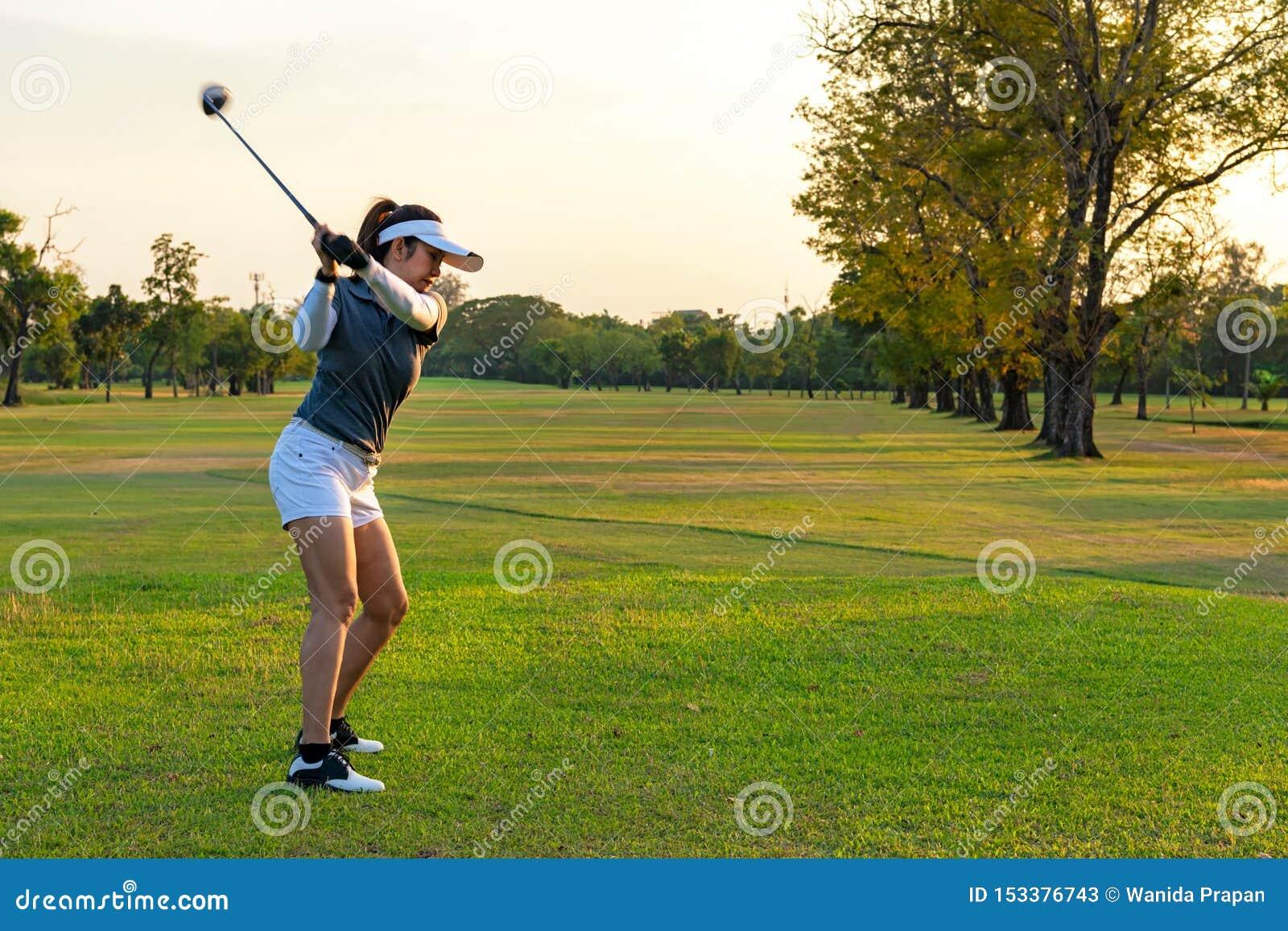 Deporte sano Jugador deportivo asi?tico del golfista de la mujer que hace la camiseta del oscilaci?n del golf apagado en el tiemp