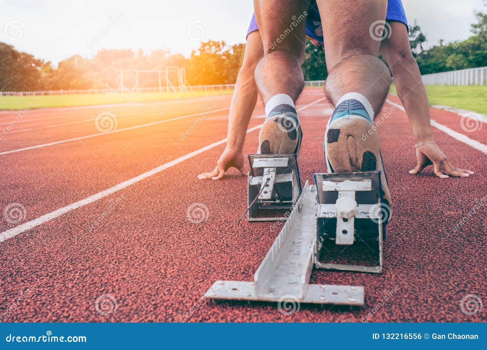 Deporte vista trasera de los pies de los hombres en el bloque el comenzar listo para un spri