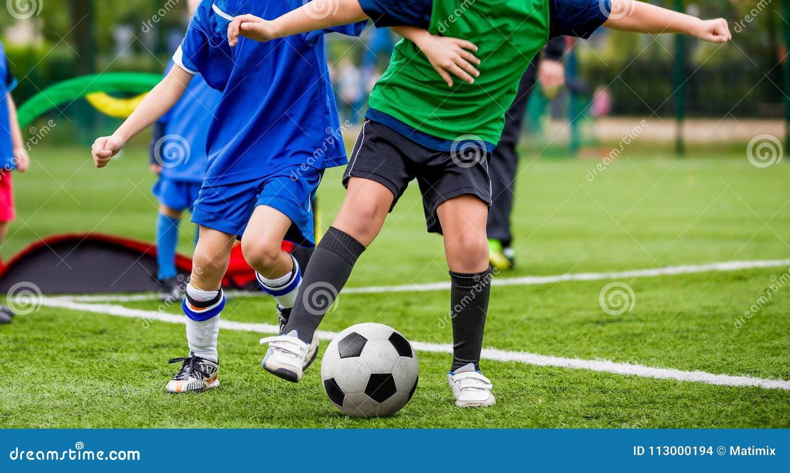 Deportes del juego de niños Niños que golpean el partido de fútbol con el pie Muchachos jovenes que juegan a fútbol en la echada