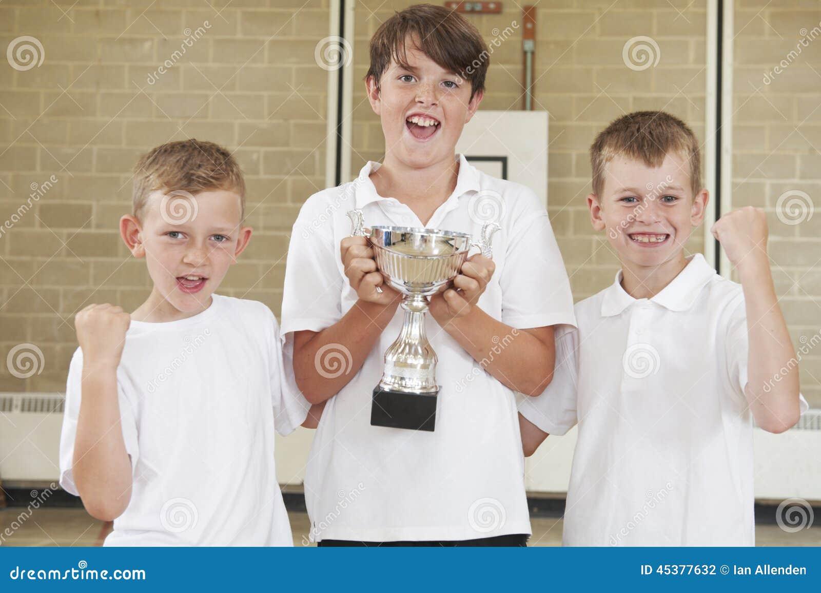 Deportes masculinos Team In Gym With Trophy de la escuela