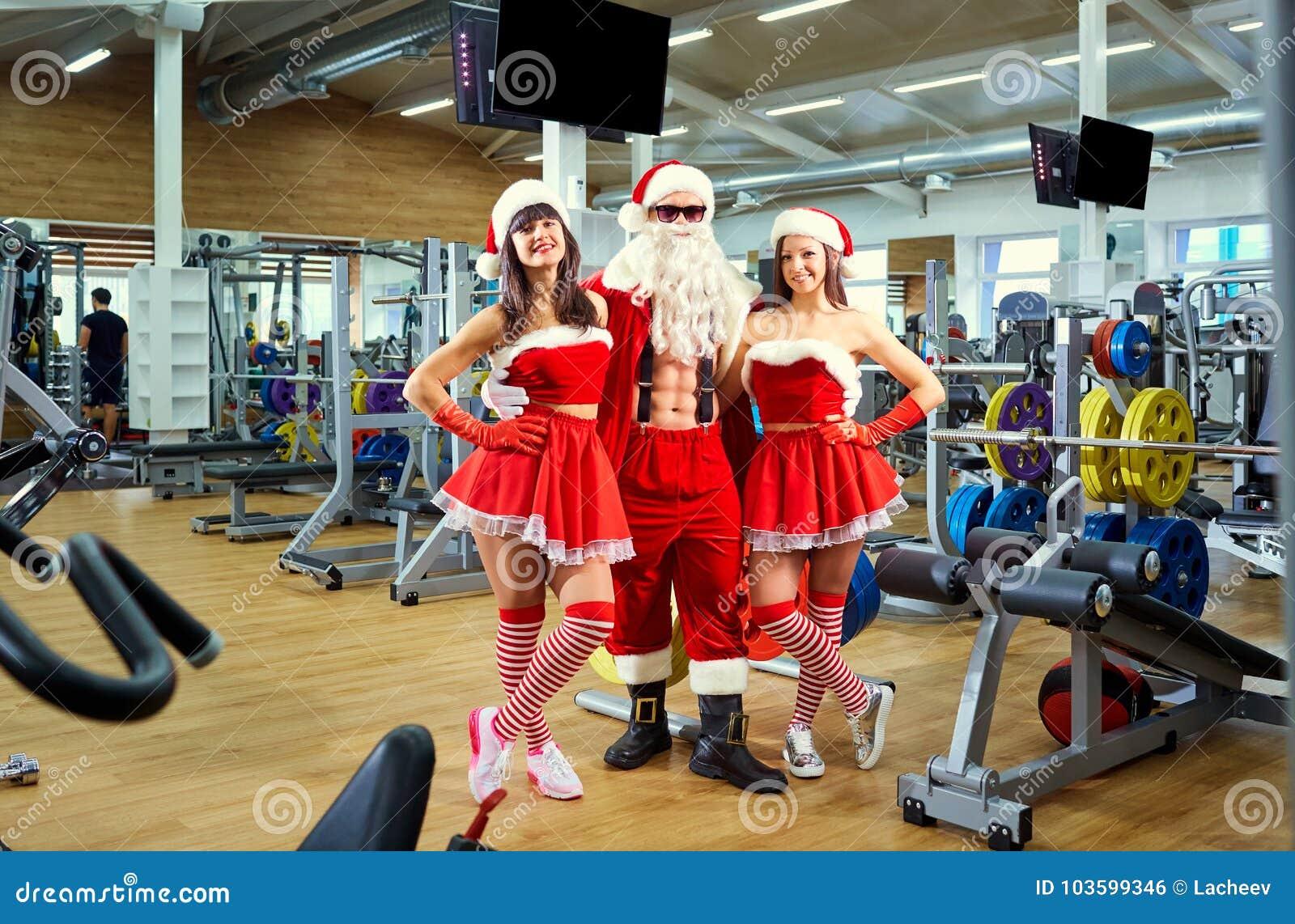 Deportes Santa Claus con las muchachas en trajes del ` s de Papá Noel en el gimnasio encendido
