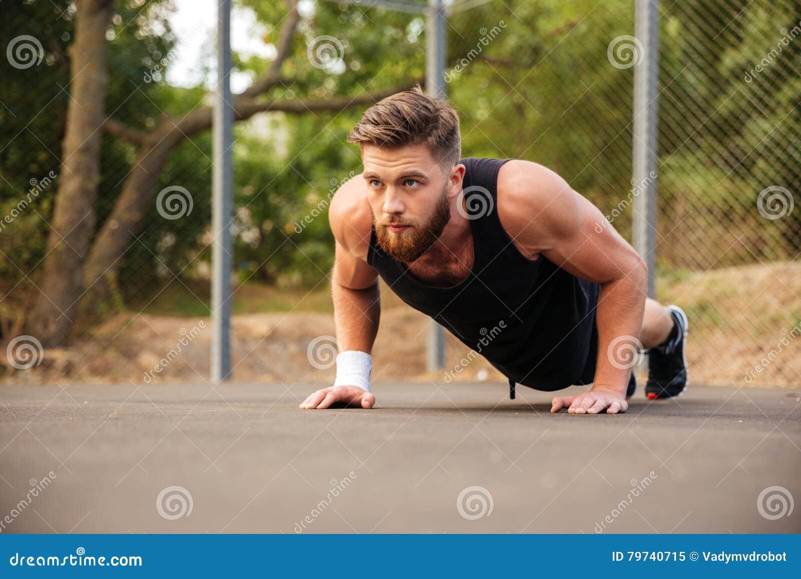 Deportista barbudo atractivo que hace pectorales al aire libre