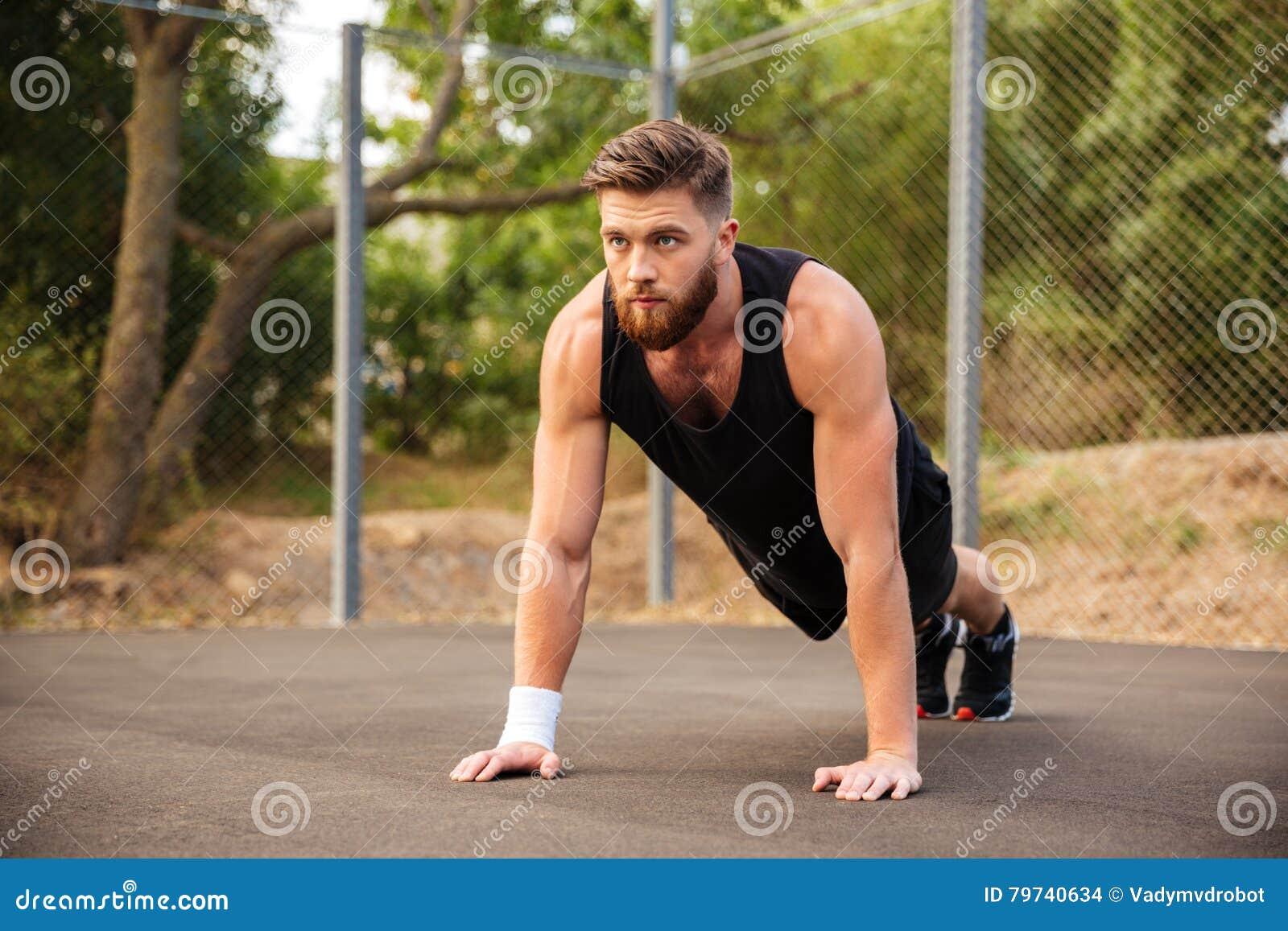 Deportista barbudo hermoso que hace pectorales al aire libre