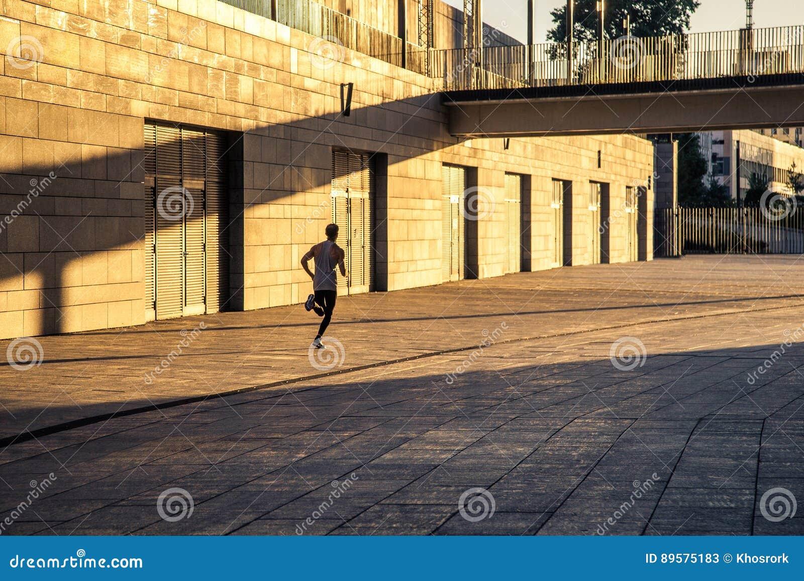 Deportista envejecido que corre en la carretera nacional, forma de vida inspirada sana de la aptitud, entrenamiento del intervalo