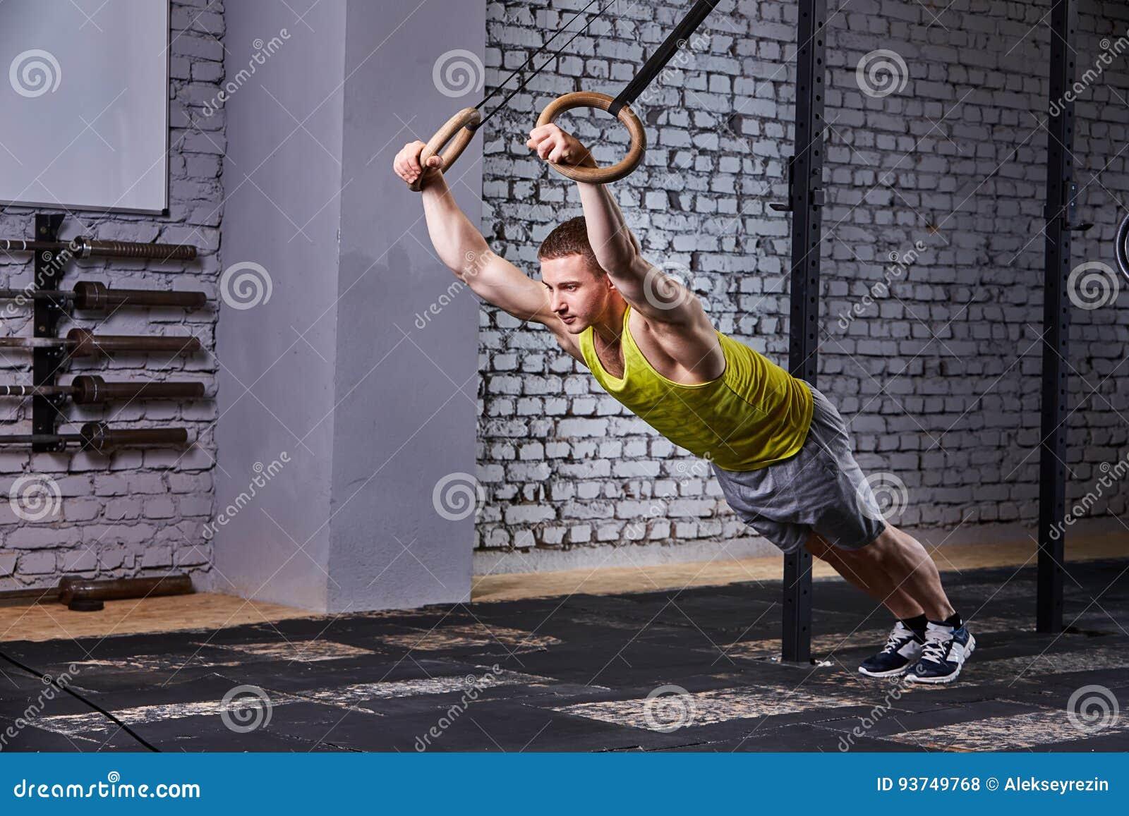 Deportista joven en el sportwear que ejercita con los anillos gimnásticos en gimnasio contra la pared de ladrillo