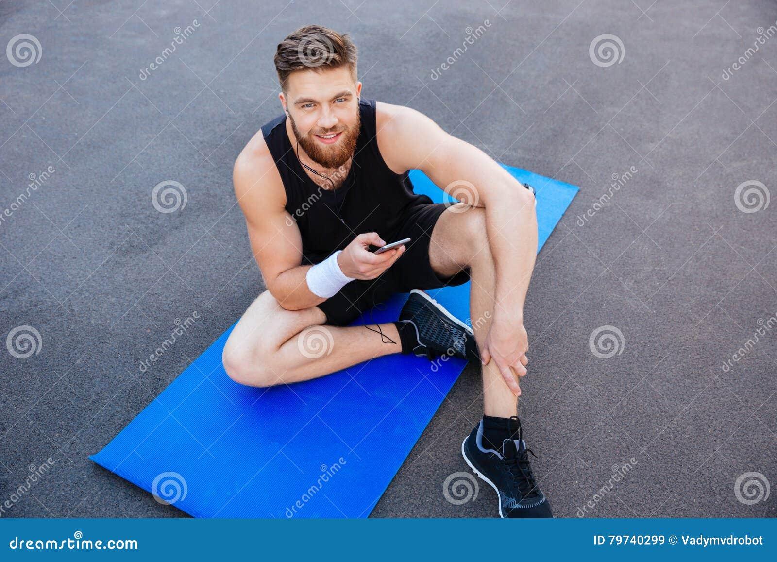 Deportista joven feliz que descansa y que usa el teléfono móvil