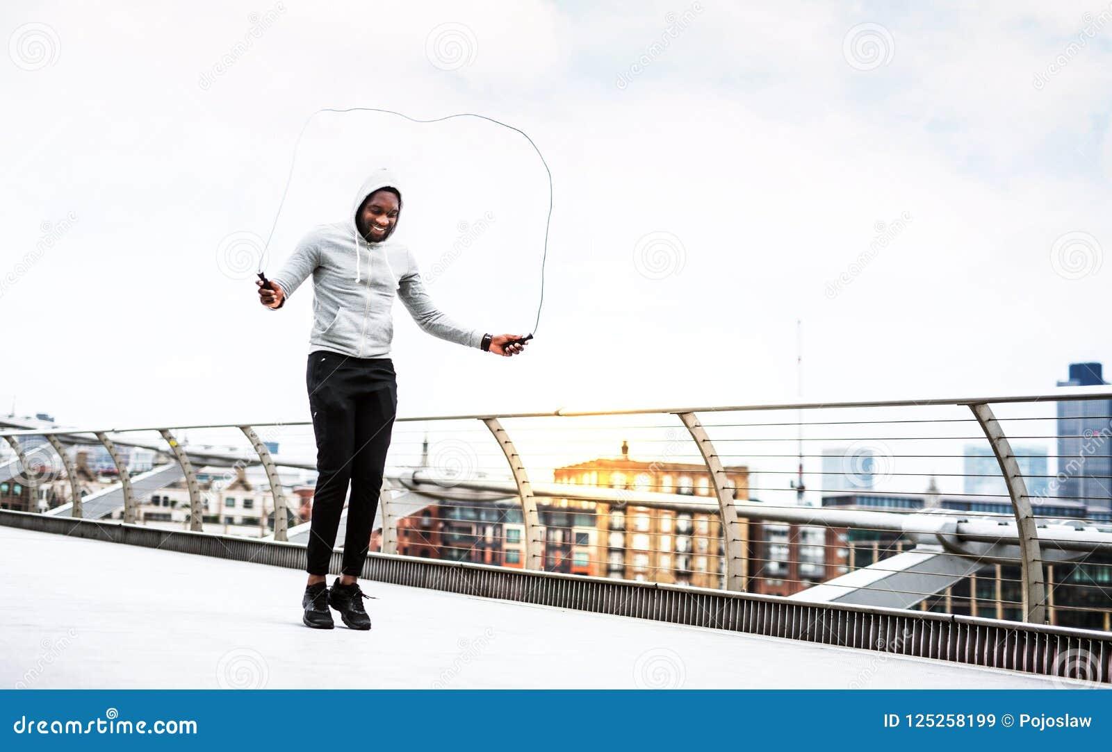 Deportista negro activo joven que salta con una cuerda en una ciudad, sudadera con capucha que lleva
