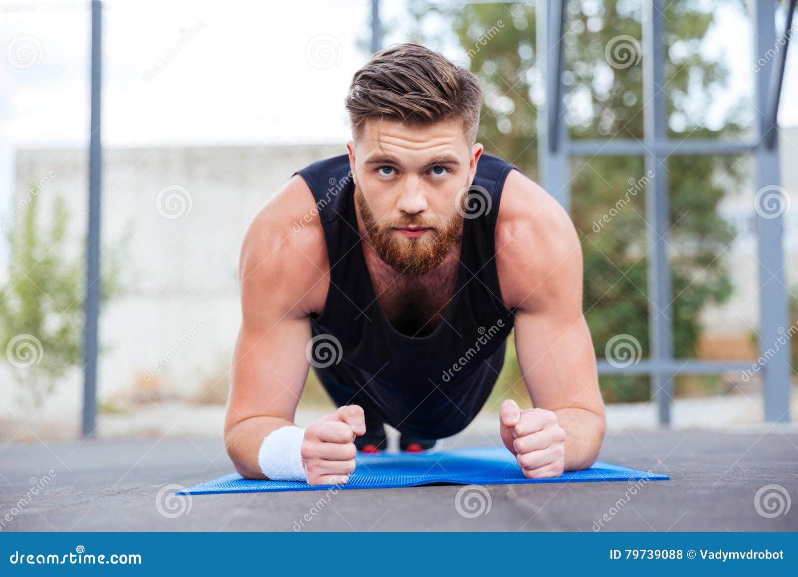 Deportista que hace ejercicio del tablón en la estera azul de la aptitud durante entrenamiento
