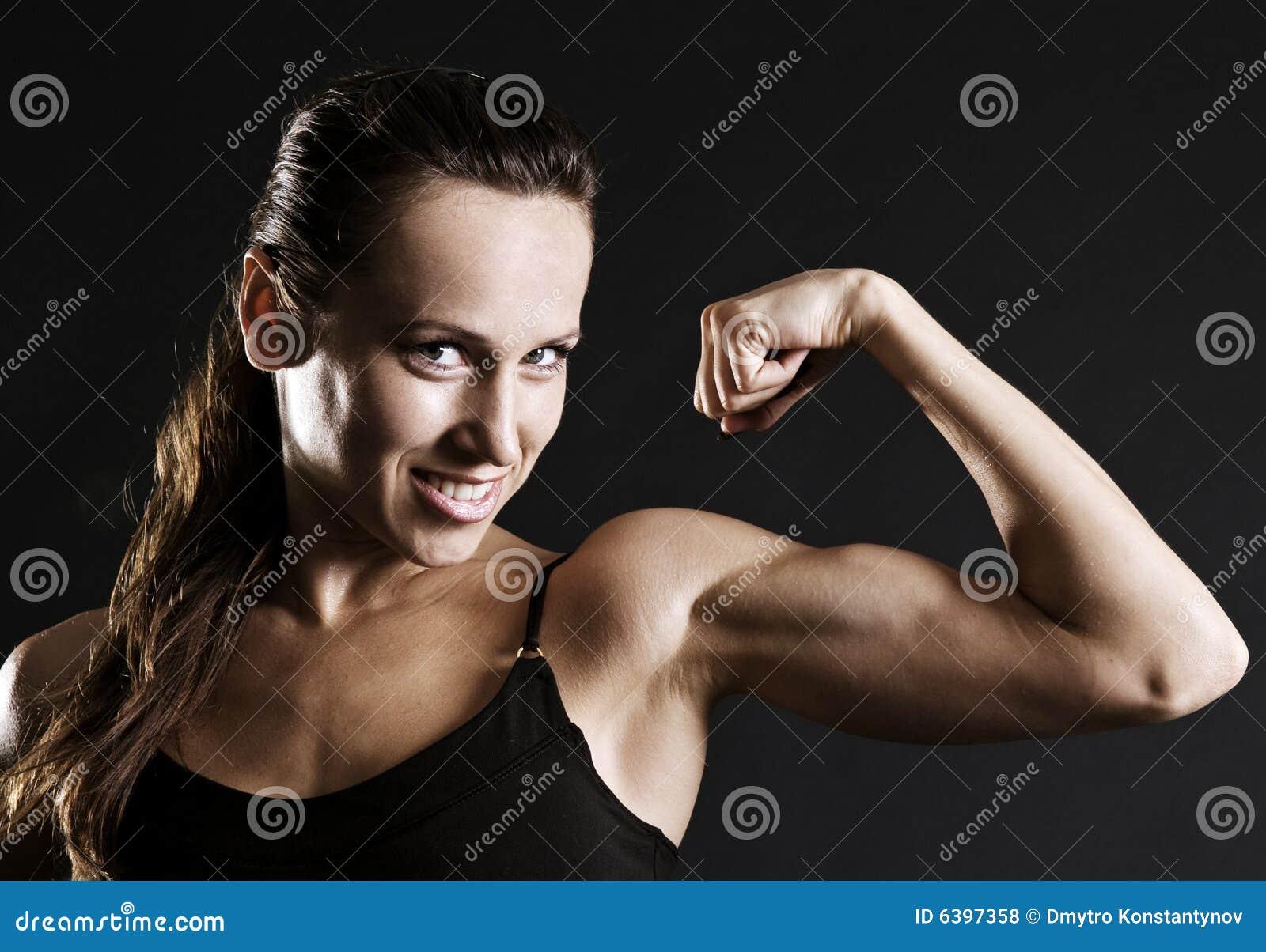 Deportista sonriente que muestra sus músculos
