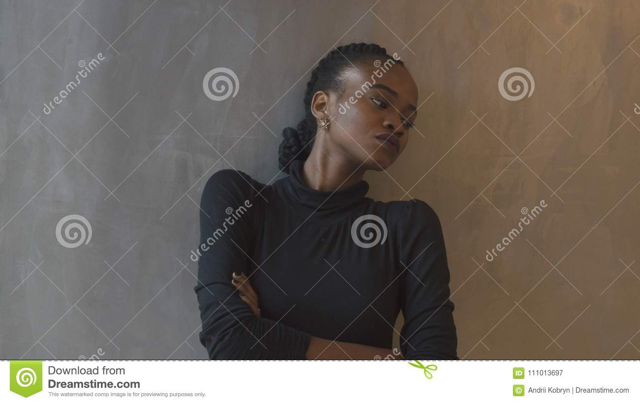 Depressed beautiful african woman with pigtails, purple lipstick and arms crossed is leaning on the gray wall and