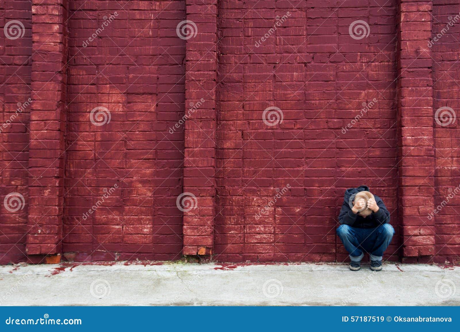 depressed child and brick wall stock photo