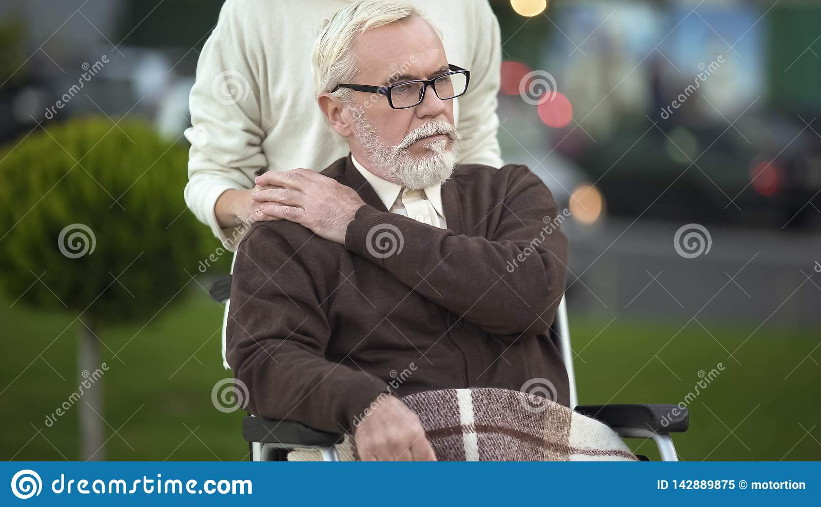 Depressed disabled elderly male in wheelchair stroking young female hand, family