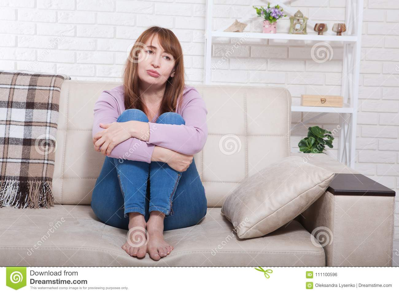Depressed And Sad Middle Aged Woman Sitting With Clamped Knees On