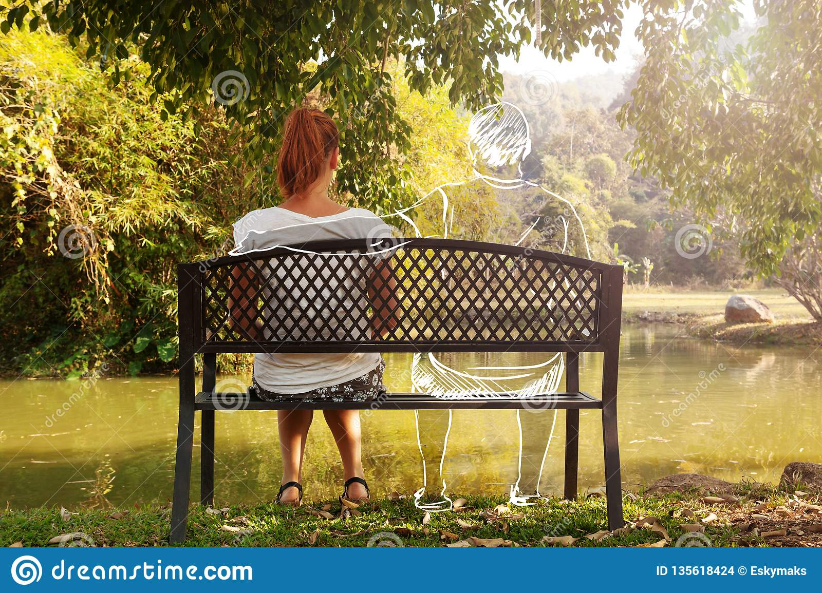 Depressed and sad young woman sitting alone on bench in the park