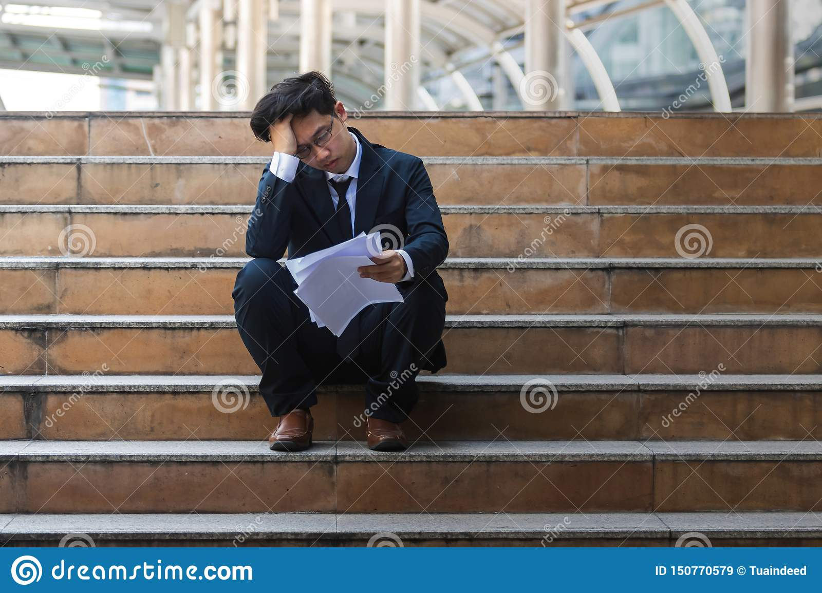 Depressed stressed young Asian business man in suit with hands on head sitting on stairs. Unemployment and layoff concept