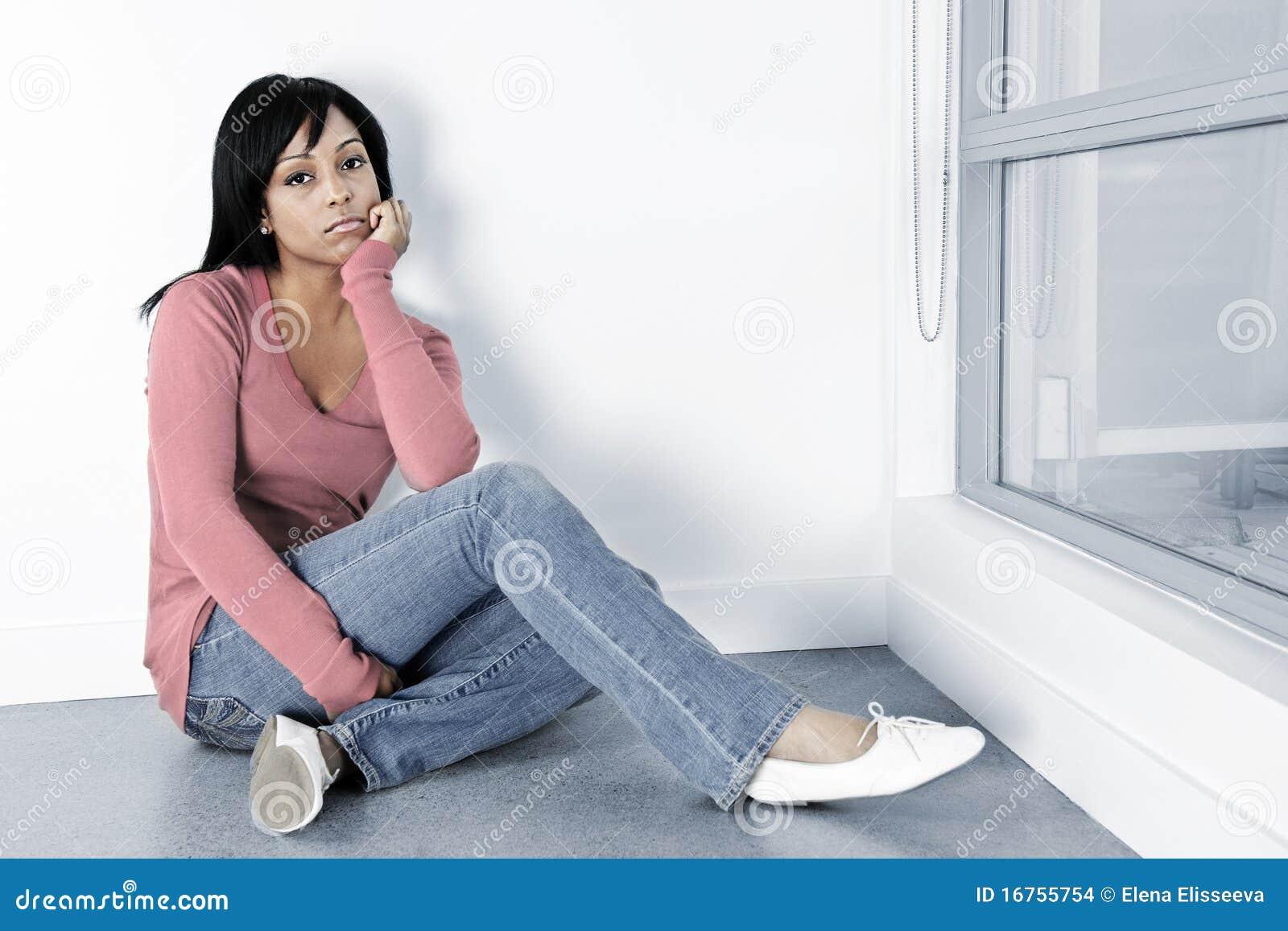 Depressed woman sitting on the floor stock photo image for On the floor on the floor