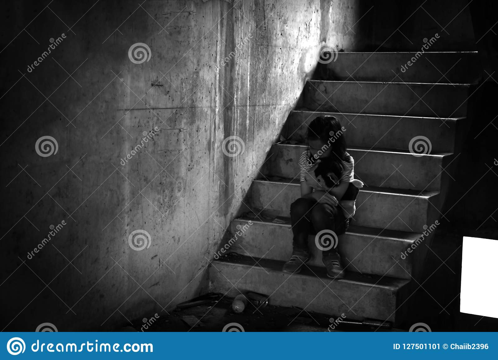 Depressed young girl sitting alone in an abandoned building
