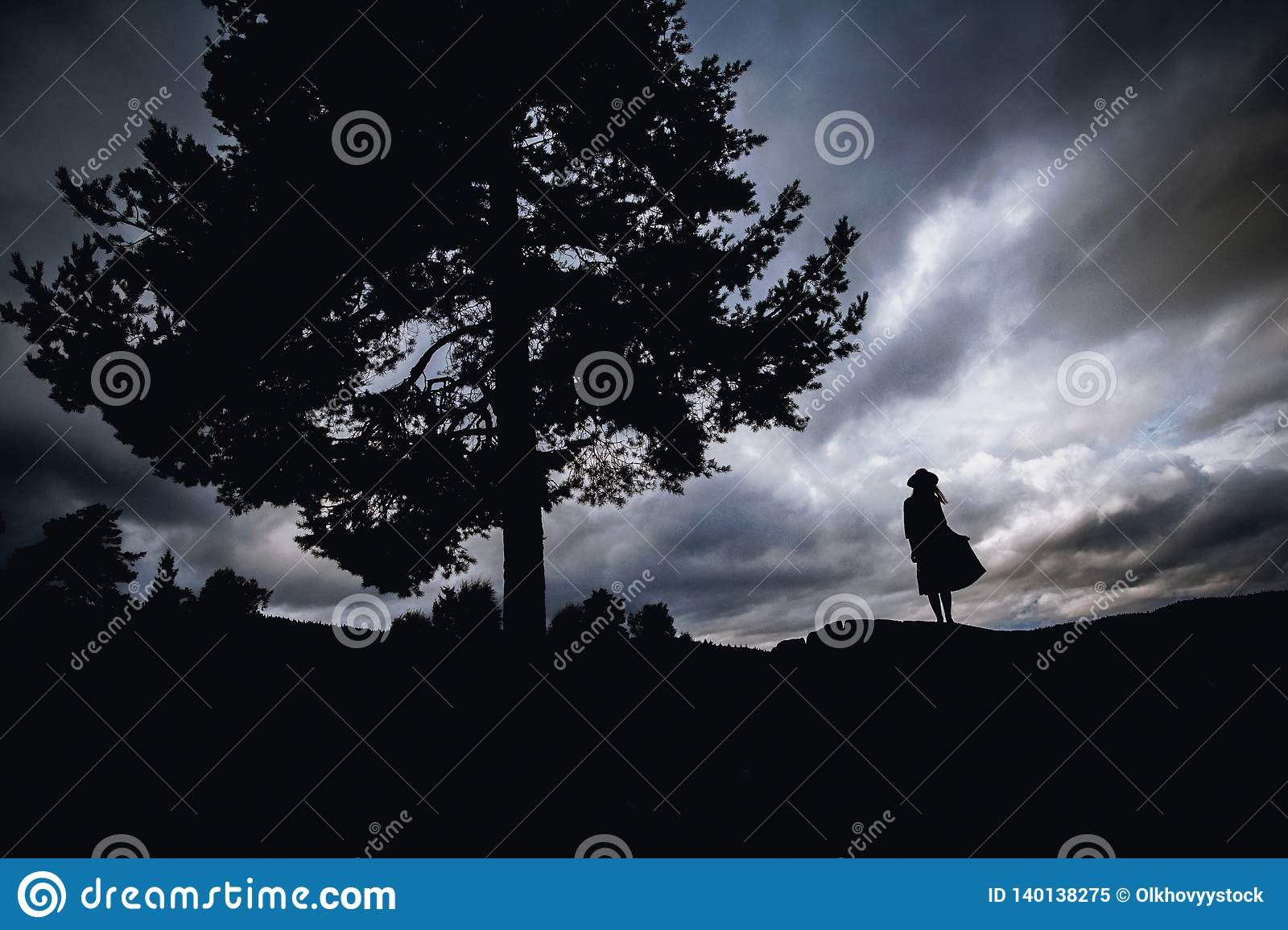 Depressed young woman sitting under the tree