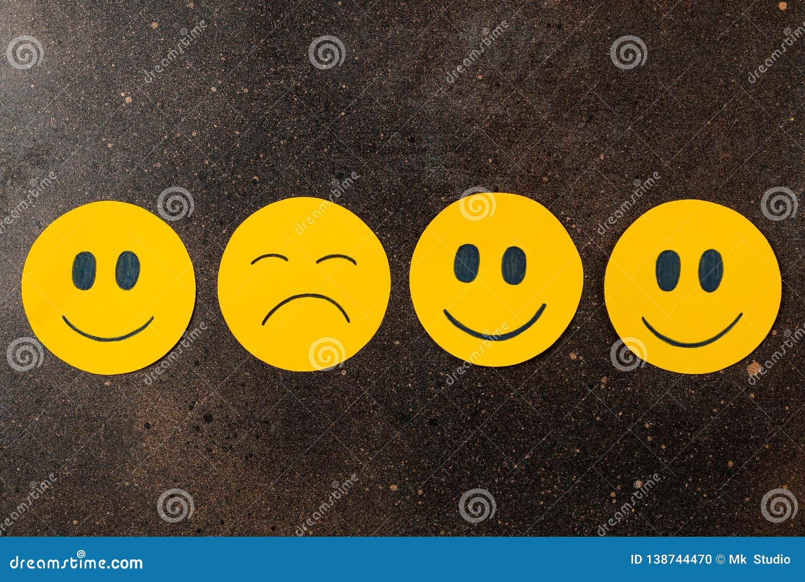 Depression Concept  Sad Smiley Among Funny Smileys On A Dark