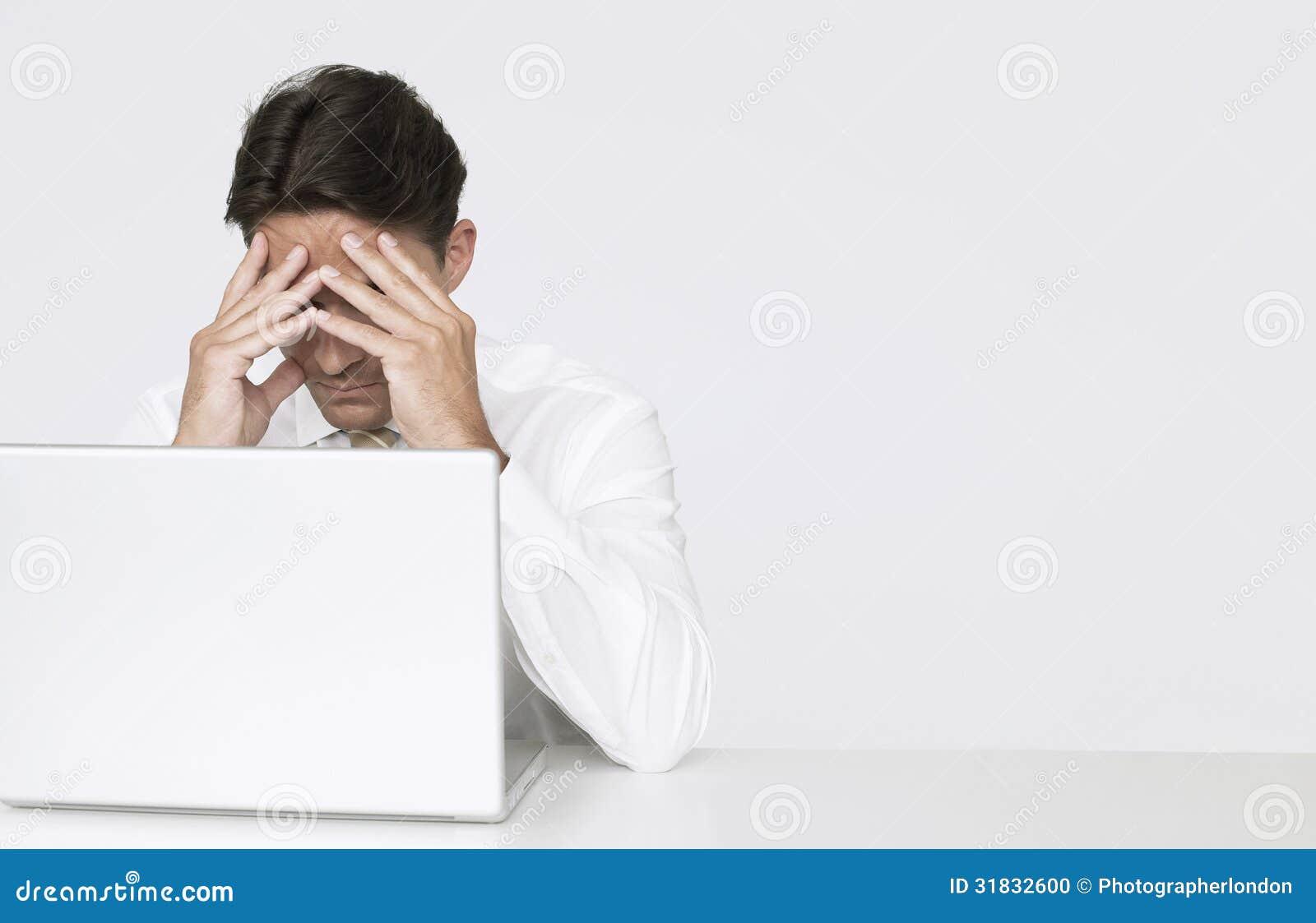 Deprimerad affärsman Sitting With Laptop på skrivbordet i regeringsställning