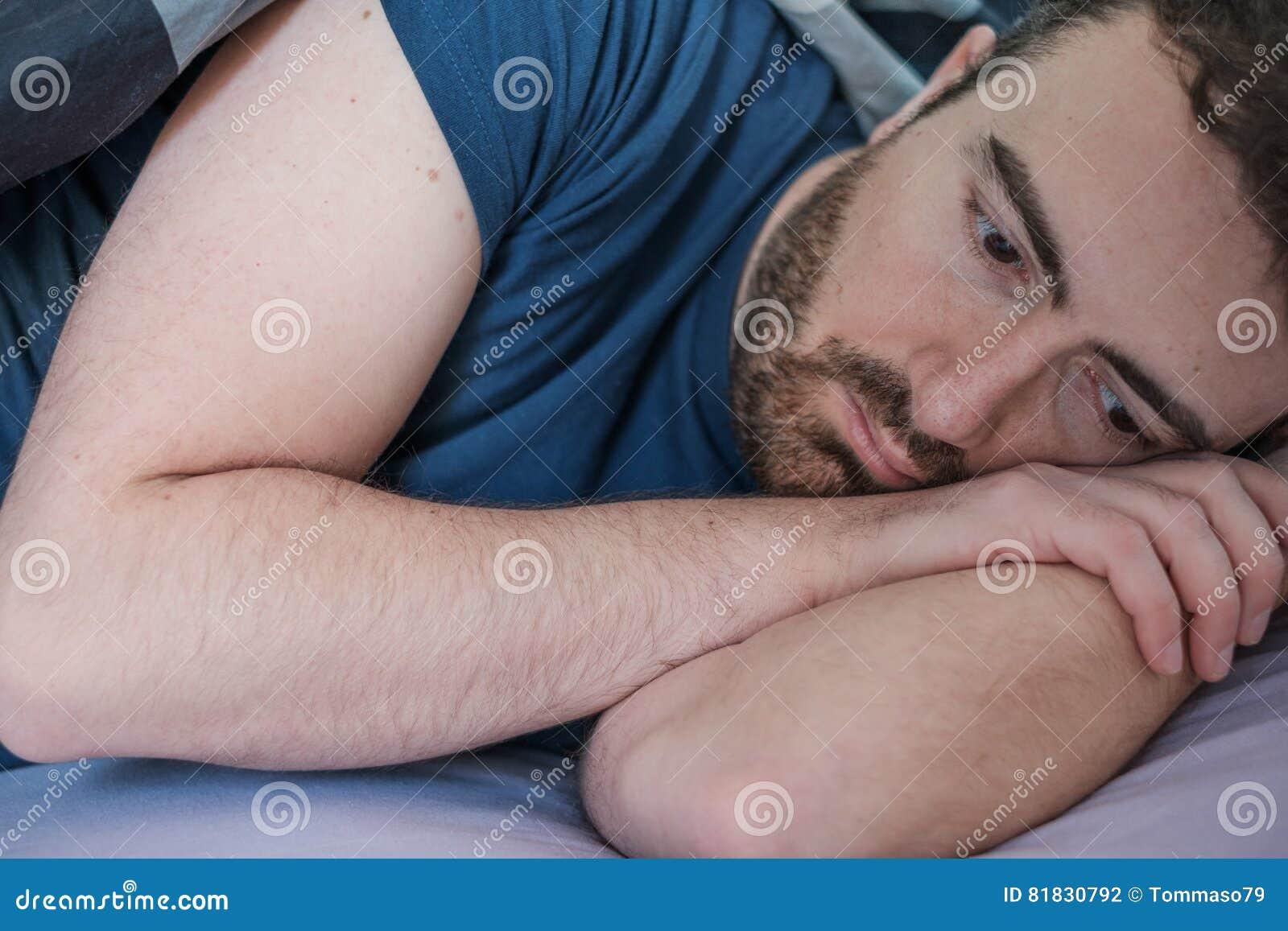 Deprimerad man som ligger i hans säng