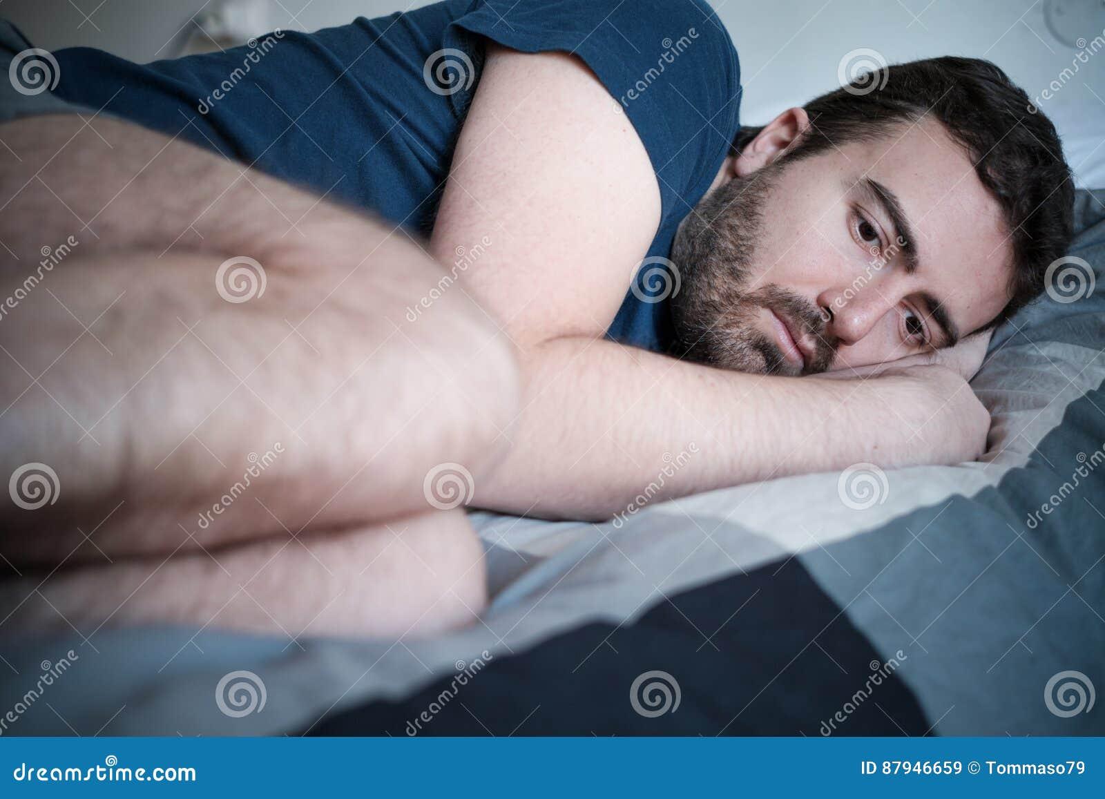 Deprimerad man som ligger i säng som känner sig dålig