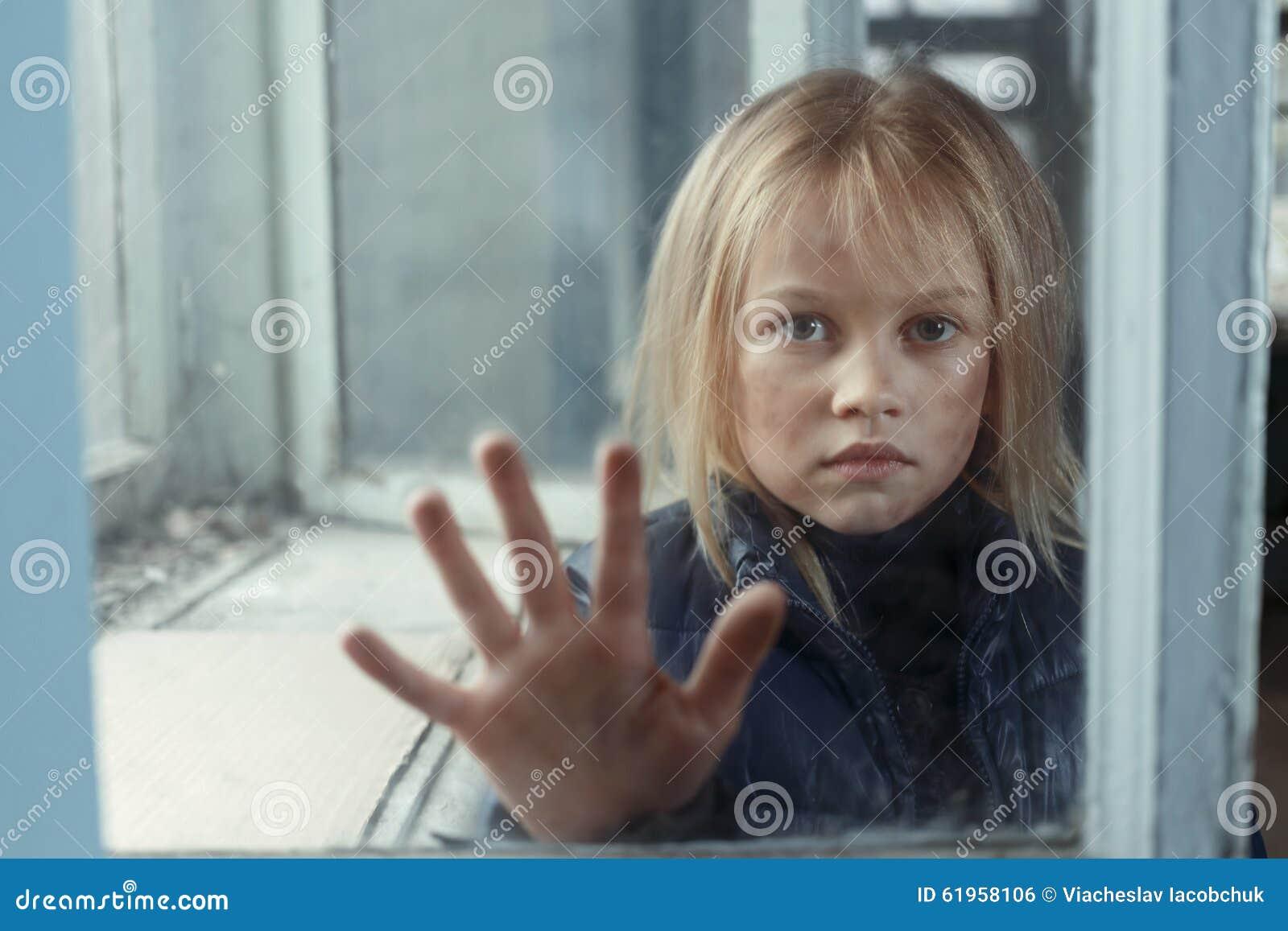 Deprimerad pootflicka som står det near fönstret
