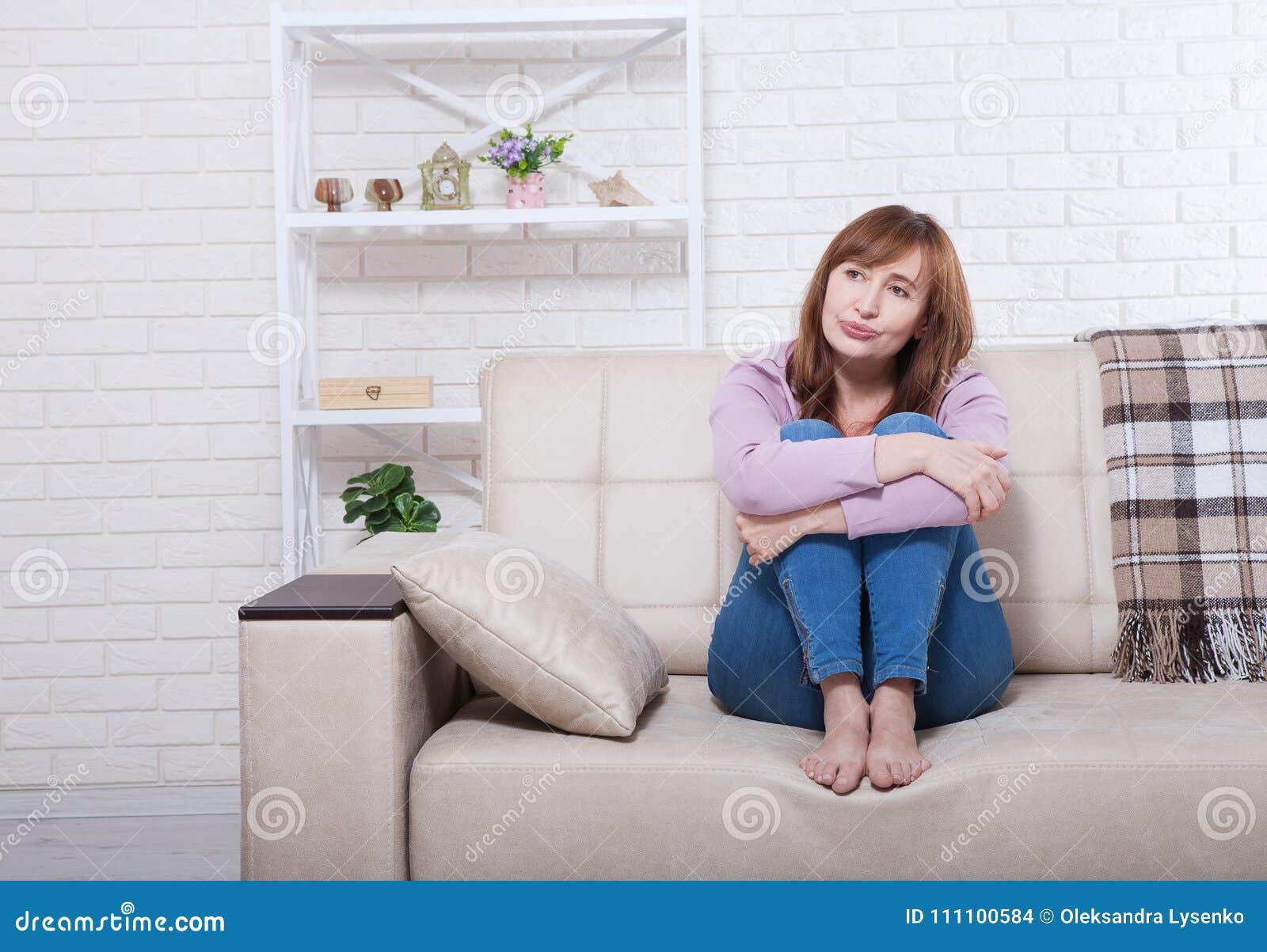 Deprimierte und traurige mittlere Greisin, die zu Hause mit festgeklemmten Knien auf Bett, Trainer, Sofa sitzt Kopieren Sie Raum