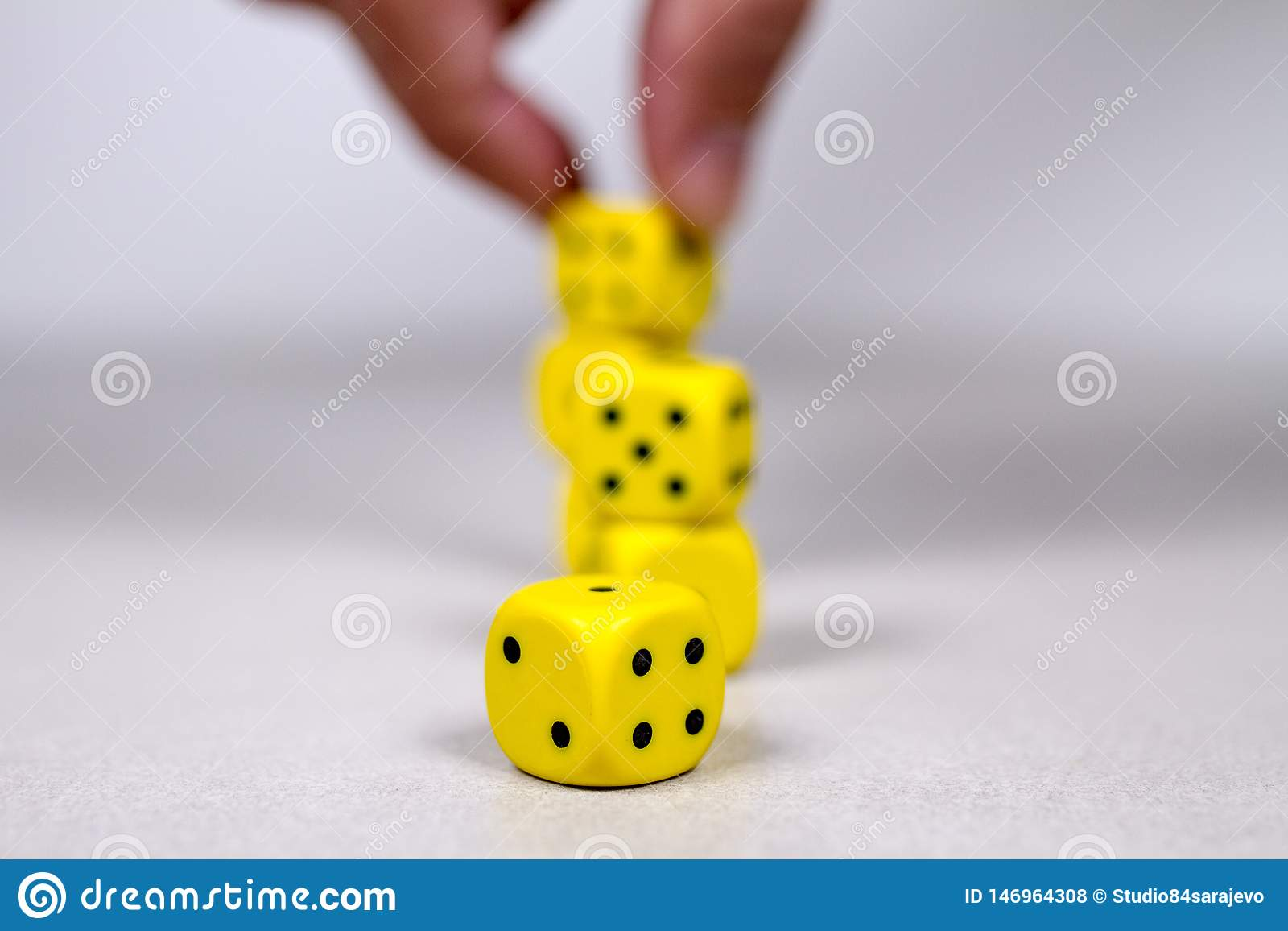 Depth of Field Man`s Mans Hand Stacking Up Yellow Dice in the Background
