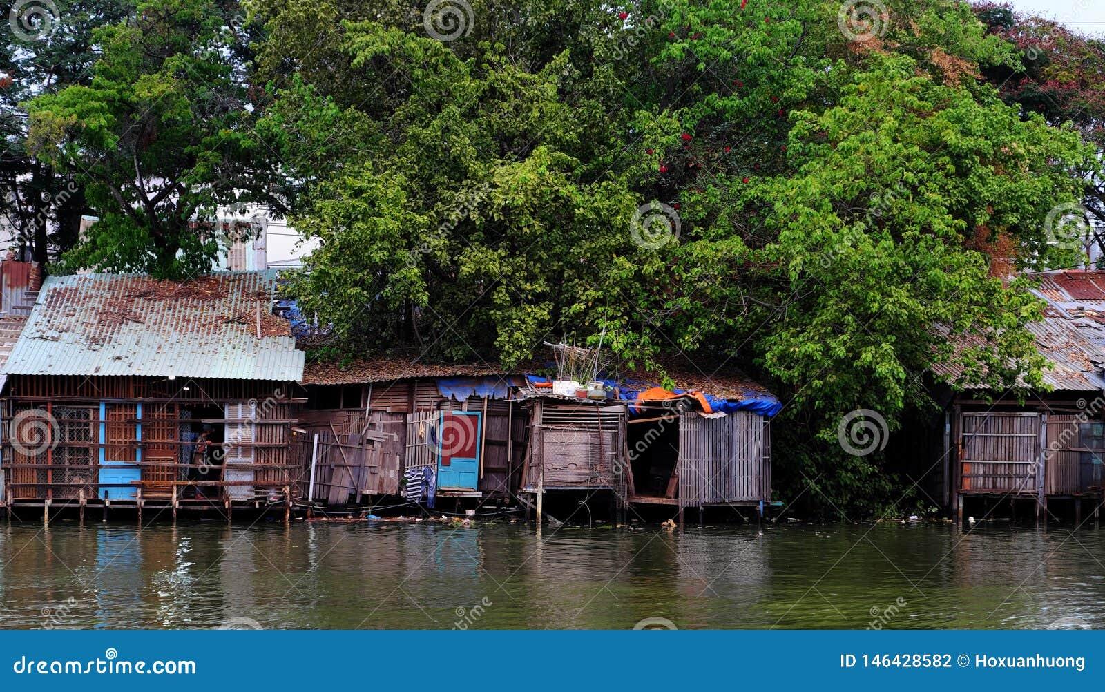 Der alte Flussufer degradieren Haus von gewölbter Blechtafel unter großem Baum