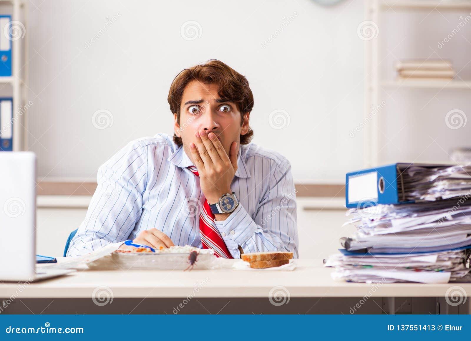 Der Angestellte, der Nahrung mit den Schaben herum kriechen isst