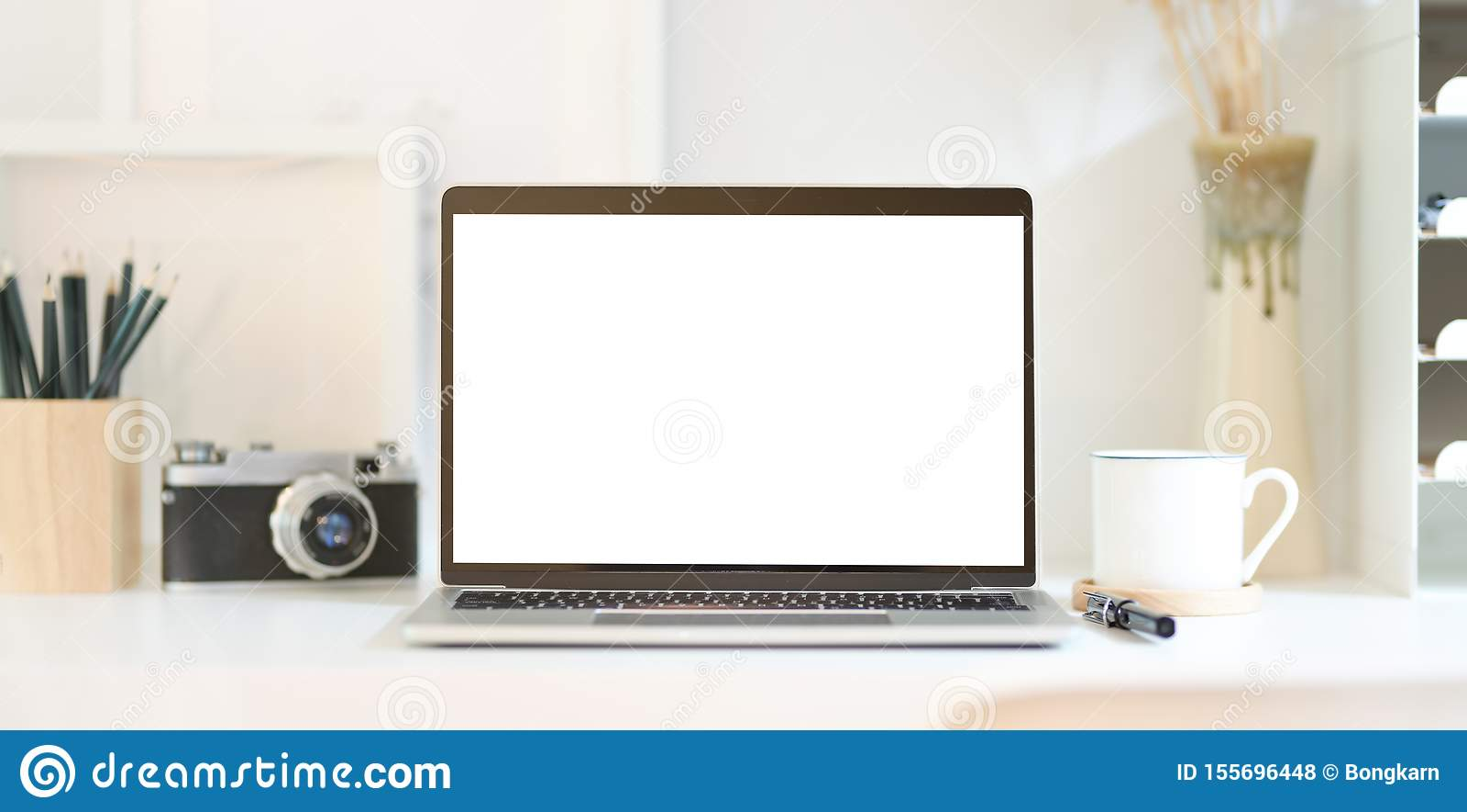Der Arbeitsplatz des Berufsfotografen mit offenem Laptop des leeren Bildschirms