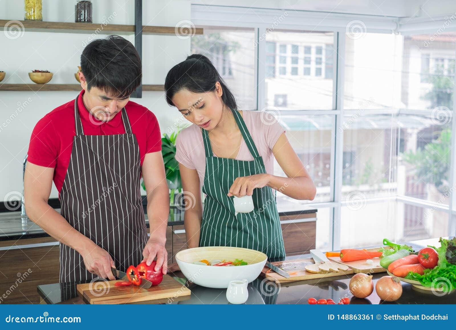 Der asiatischen Paare im Schutzblech, machen Salate zusammen Mann bereiten vor sich, Gem?se mit Messern zu schneiden Frauenmischu