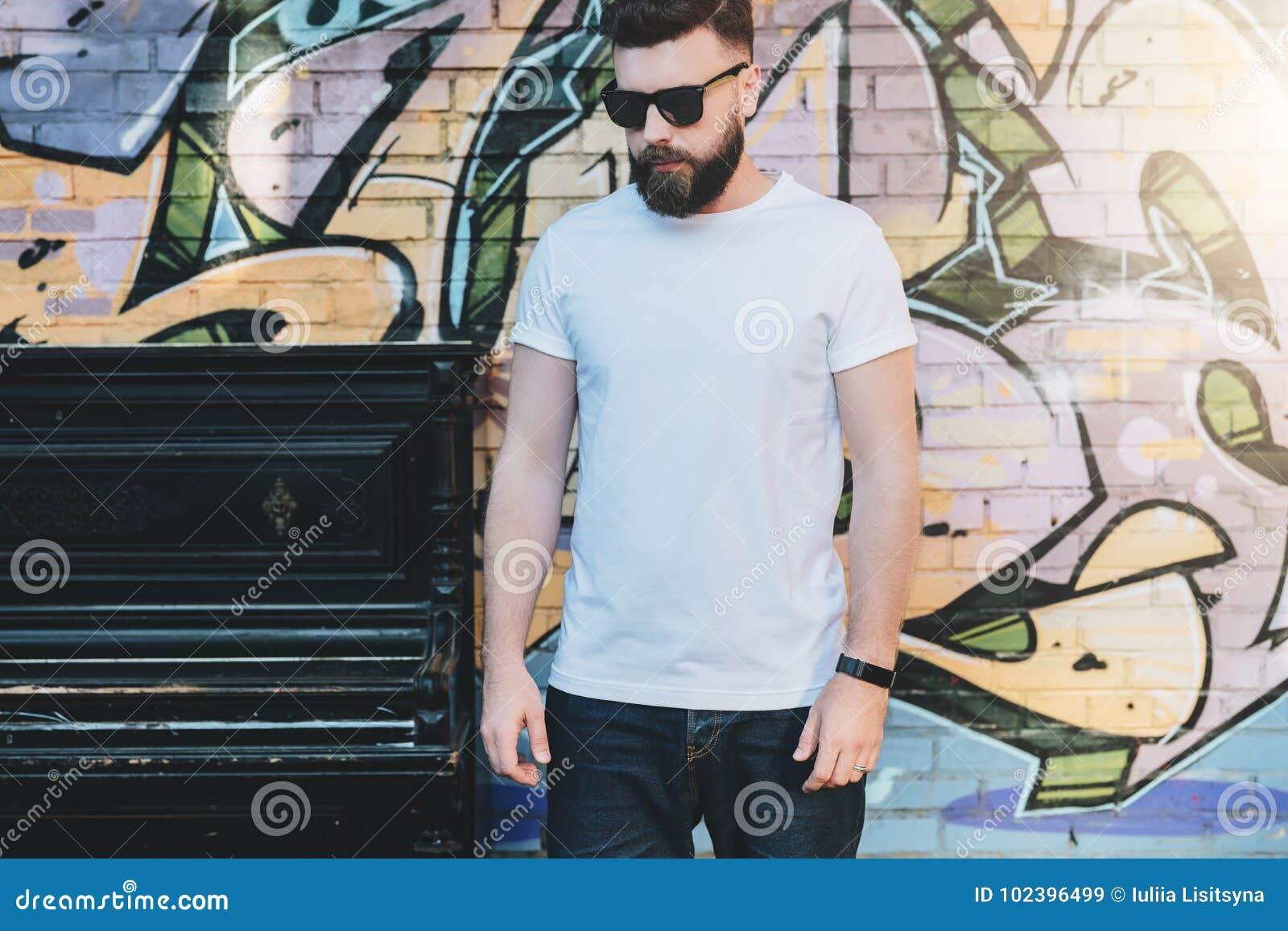 Der bärtige Hippie-Mann, der im weißen T-Shirt gekleidet wird, ist Stände gegen Wand mit Graffiti Spott oben Raum für Logo, Text,