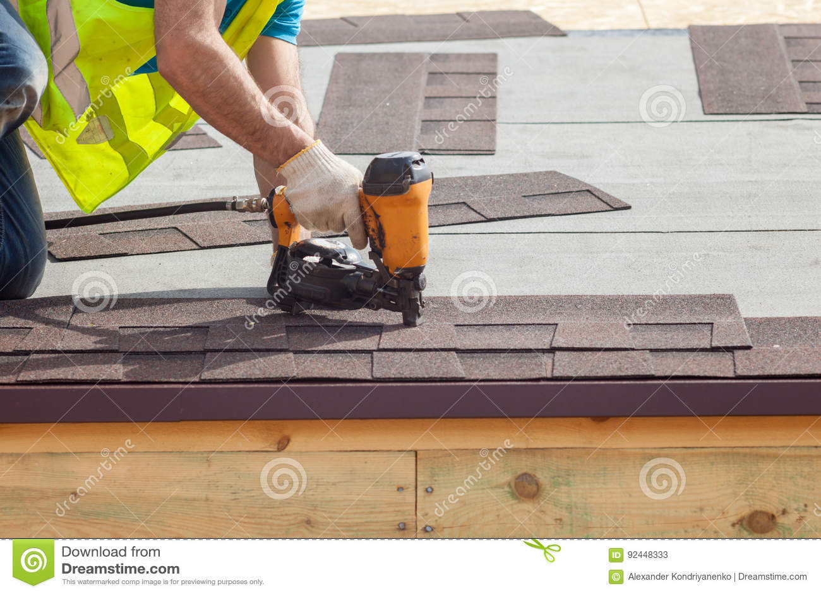 Der Bauarbeiter, der die Asphaltdeckungsschindeln mit Nagel setzt, schießen auf einem neuen Rahmenhaus