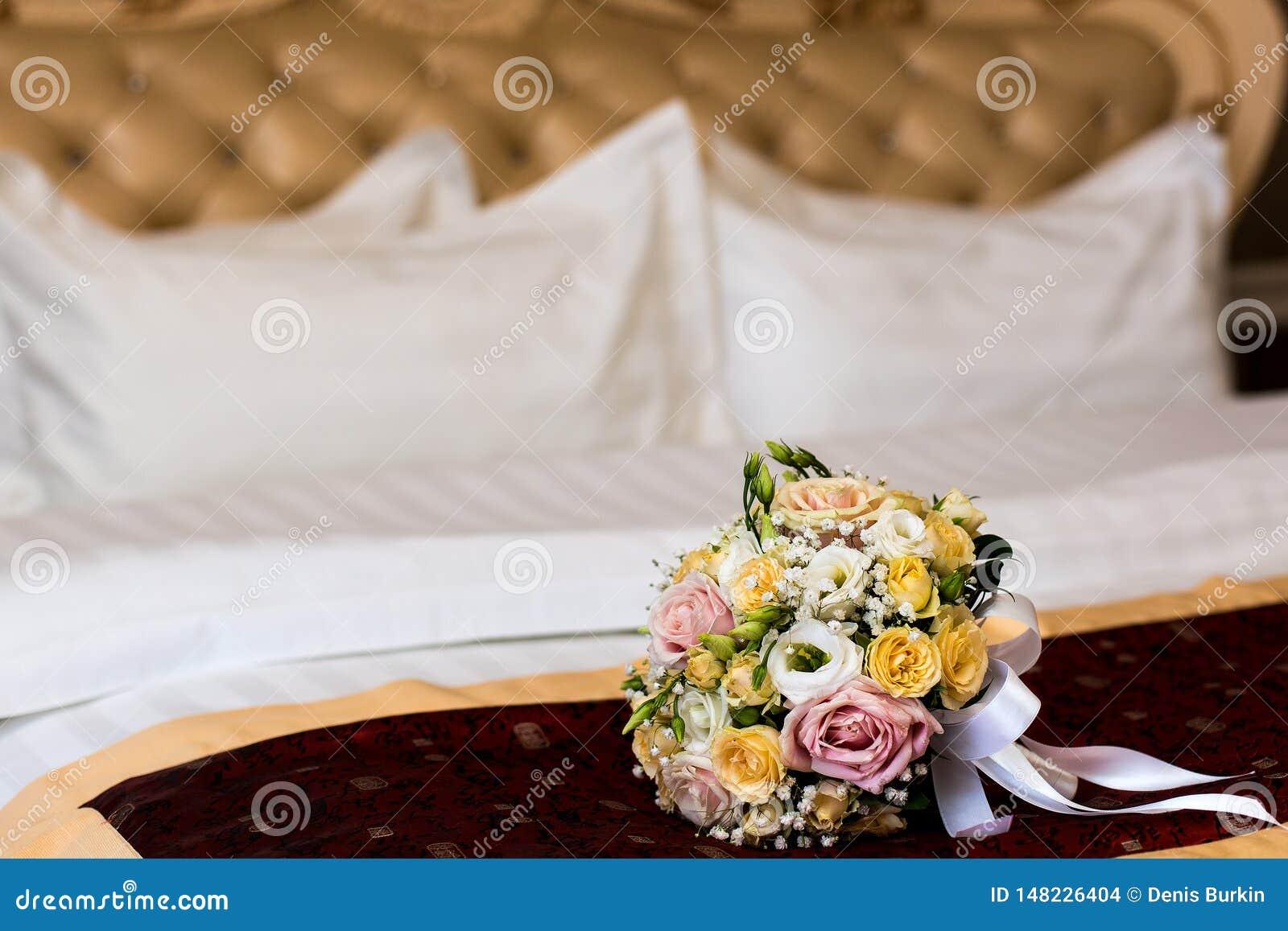 Der Blumenstrauß der Braut auf dem Bett entkleidete wedding Kleidung der Blumenstrauß der Braut auf dem Bett Blumen f?r Hochzeit