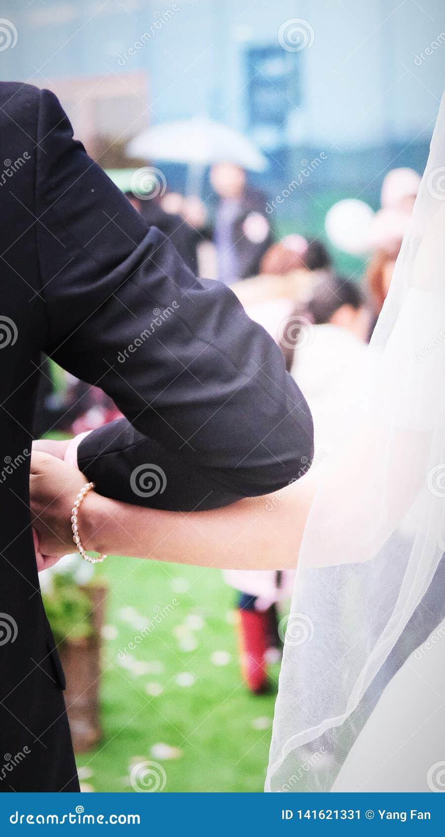 Der Bräutigam hält die Bräute übergeben an der Hochzeit