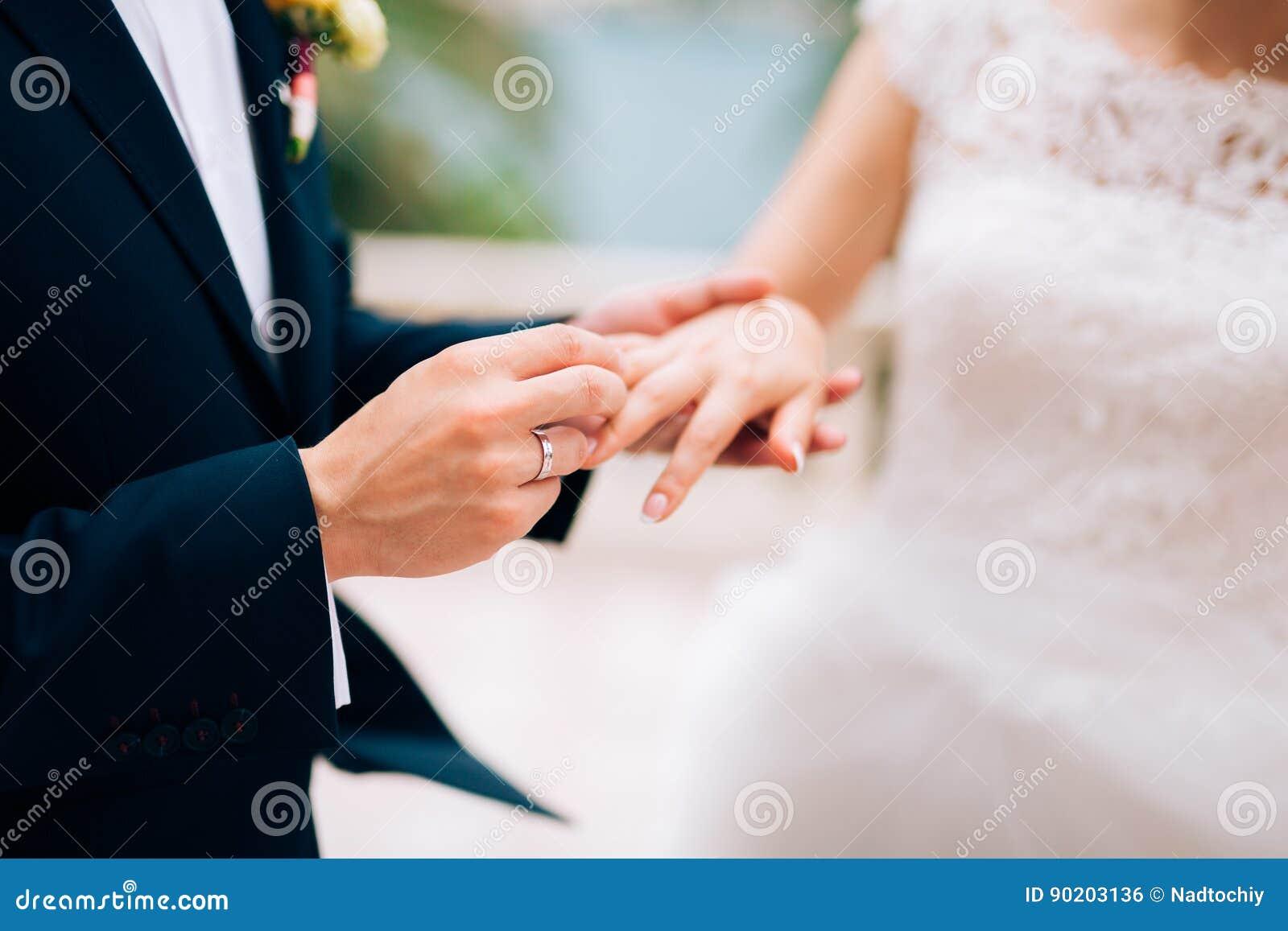 Der Bräutigam kleidet einen Ring auf dem Finger der Braut an einer Hochzeit