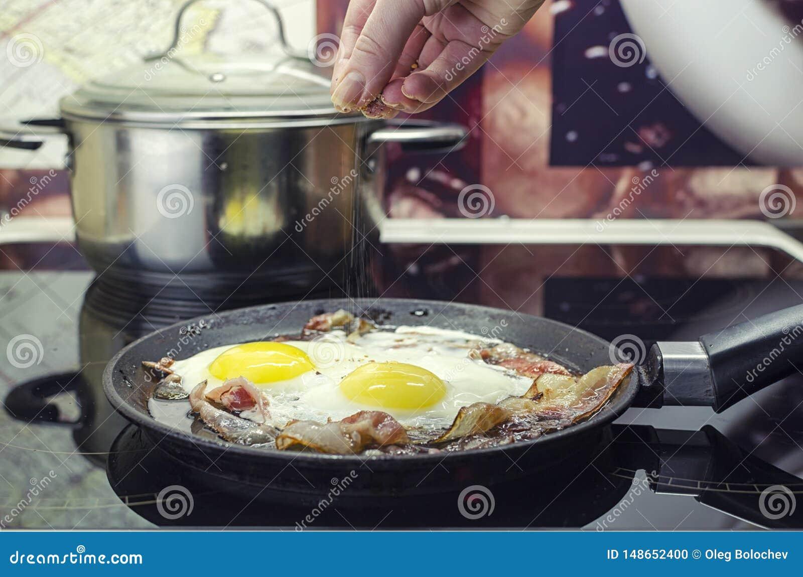 Der Chef salzt die Spiegeleier in einer Bratpfanne, kochen den Speck und Spiegeleier in der Bratpfanne, kochend in der K?che, set