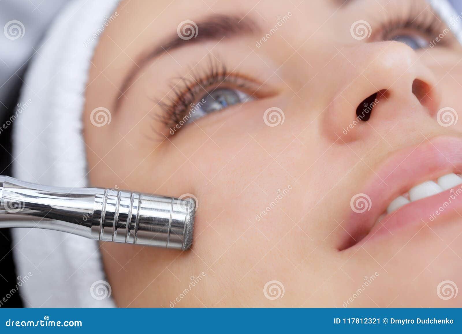 Der Cosmetologist macht das Verfahren Microdermabrasion von der Gesichtshaut einer schönen, jungen Frau