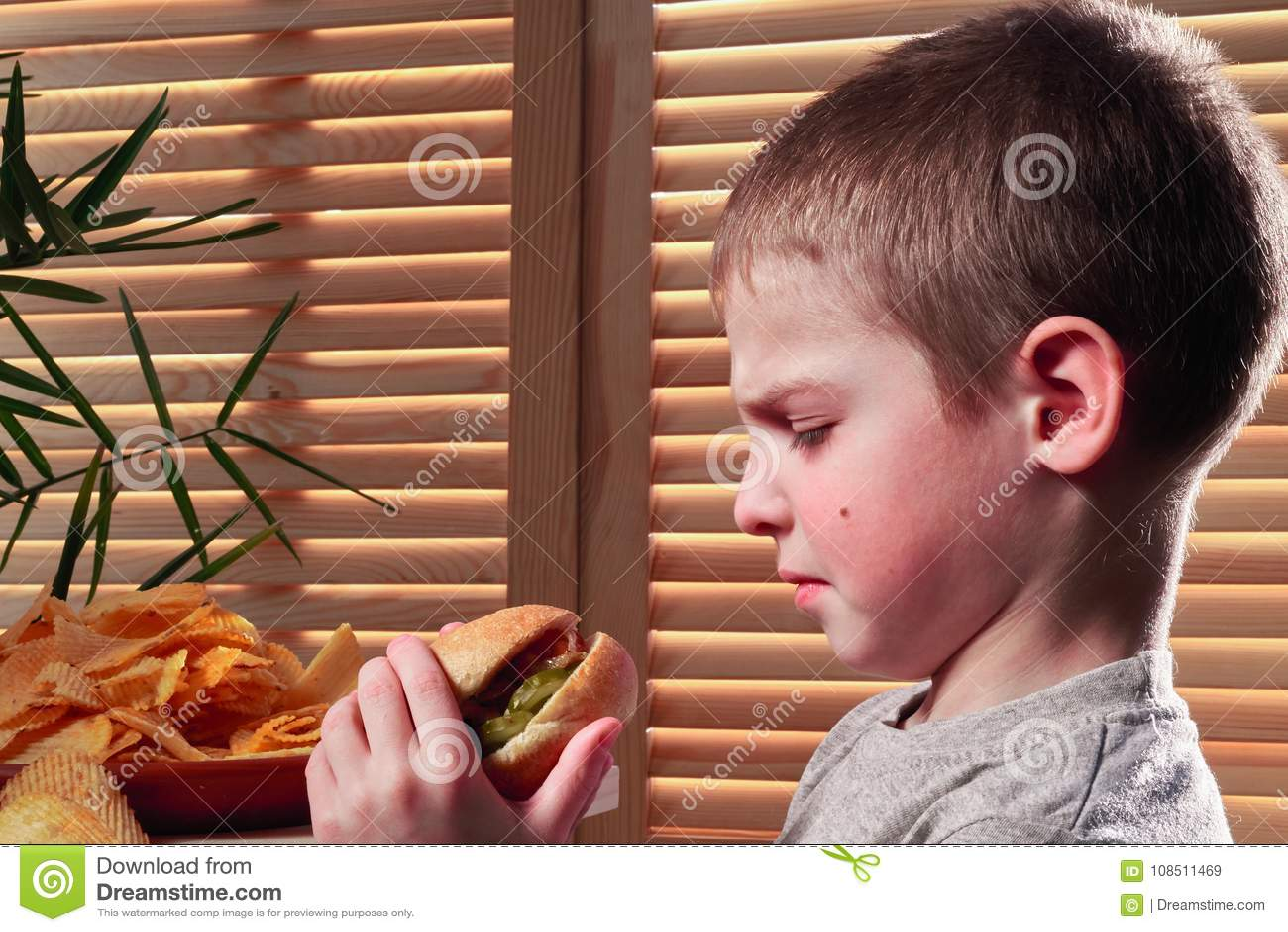 Der die Stirn runzelnde Junge betrachtet das Würstchen Kind starrt mit Ekel entlang des geschmacklosen Lebensmittels im Café an G